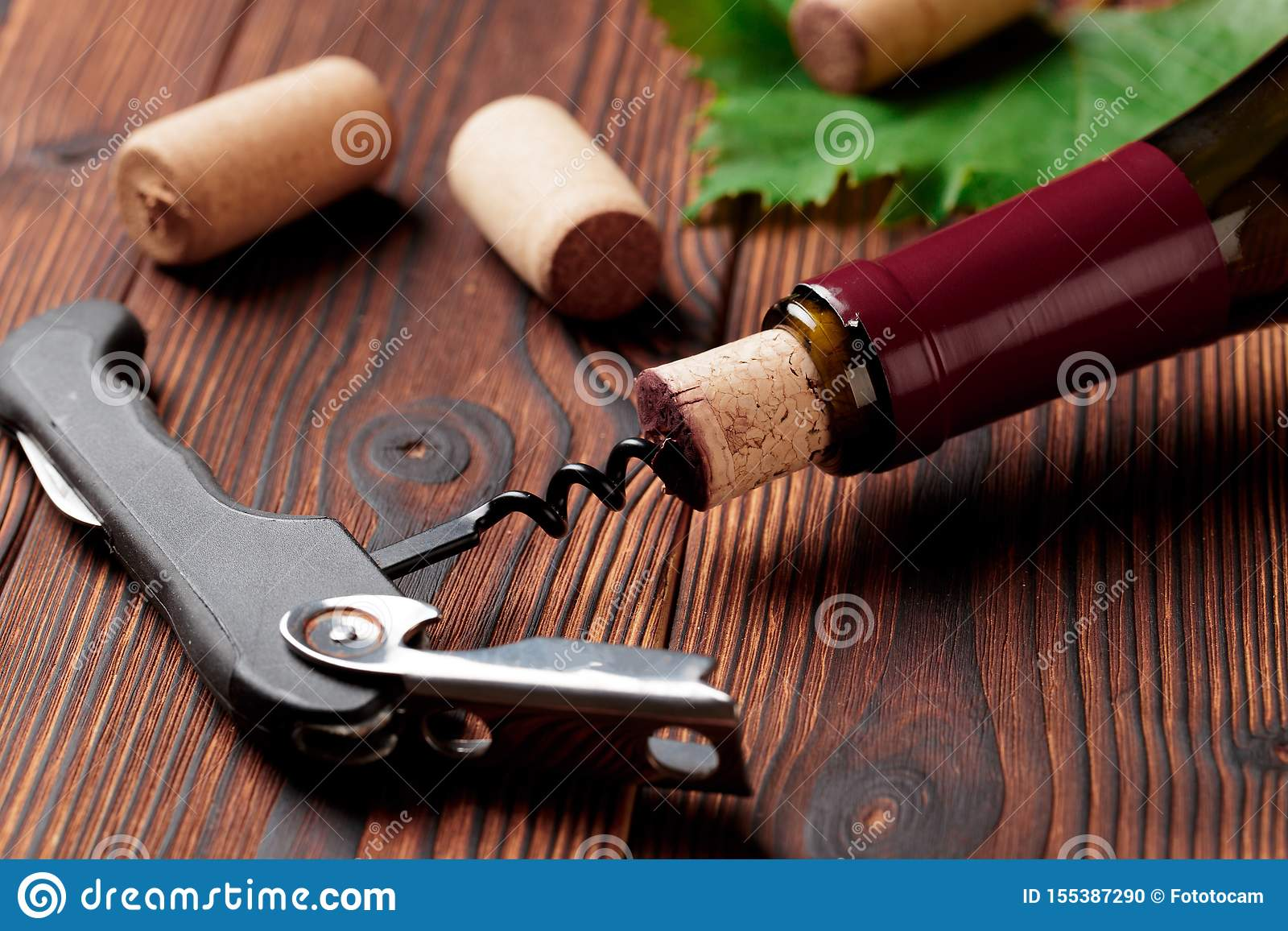 Corkscrew and bottle of wine on the board - Image