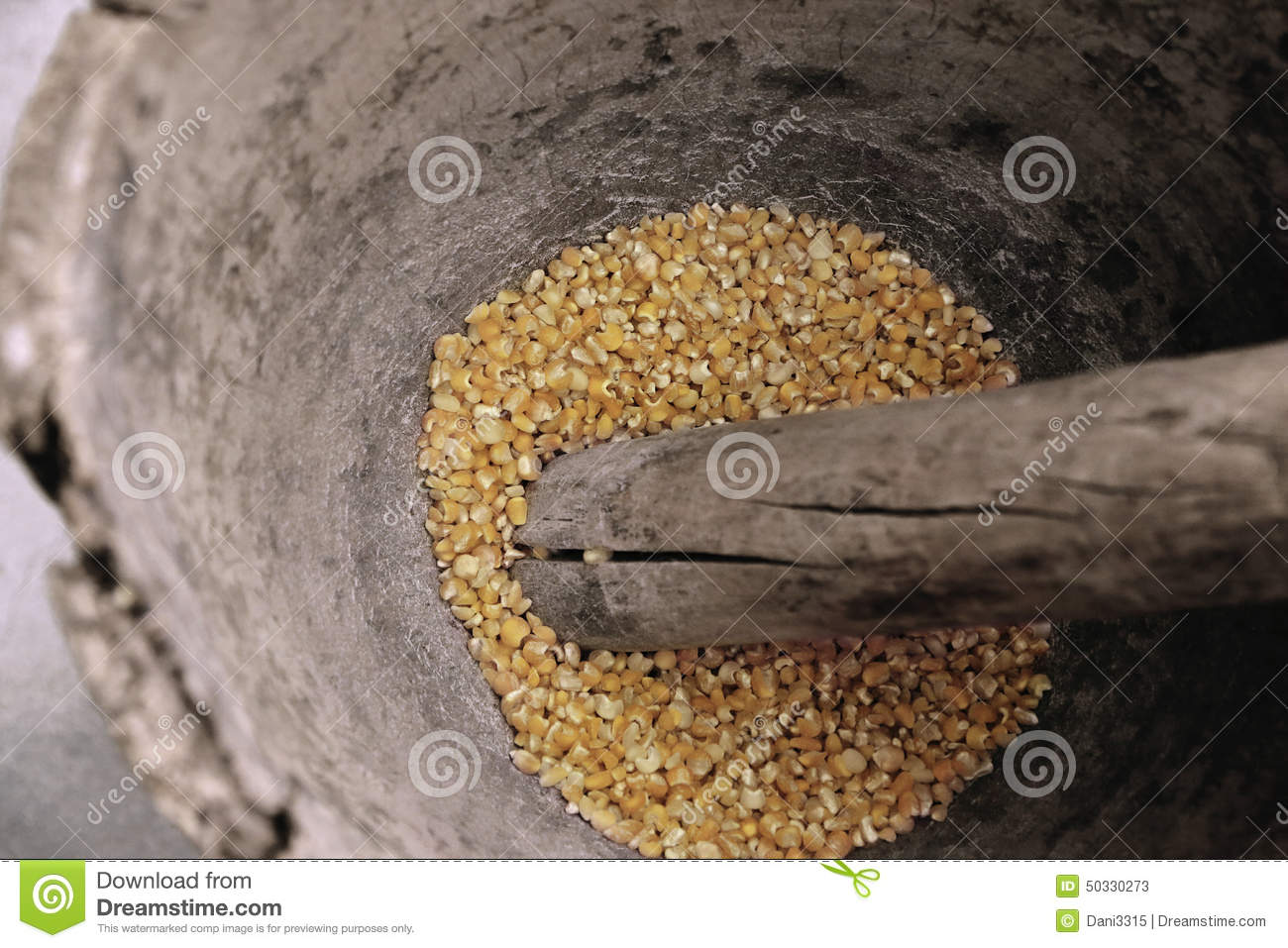 Corn Being Grinded With Mortar And Pestle Made Of Wood To