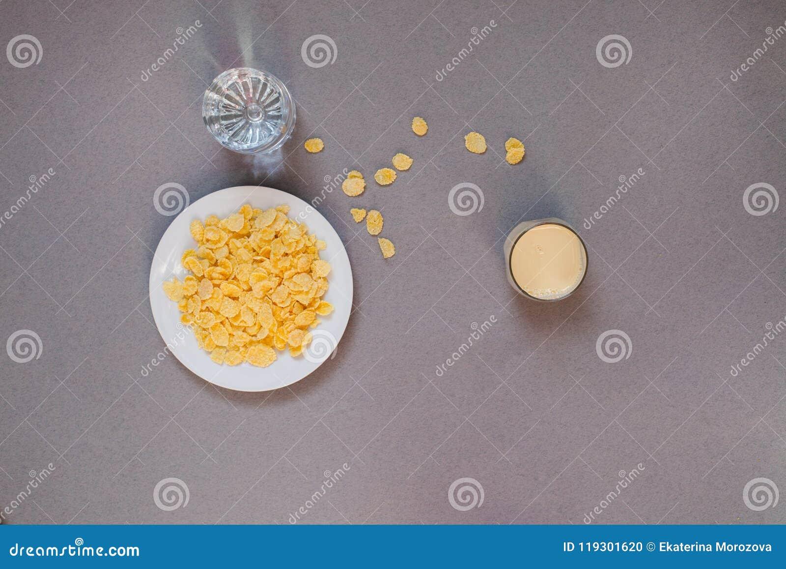 Corn-Flakes in einer weißen Schale und in einem Glas mit Wasser auf einem grauen Hintergrund, Ästhetik von Chaos