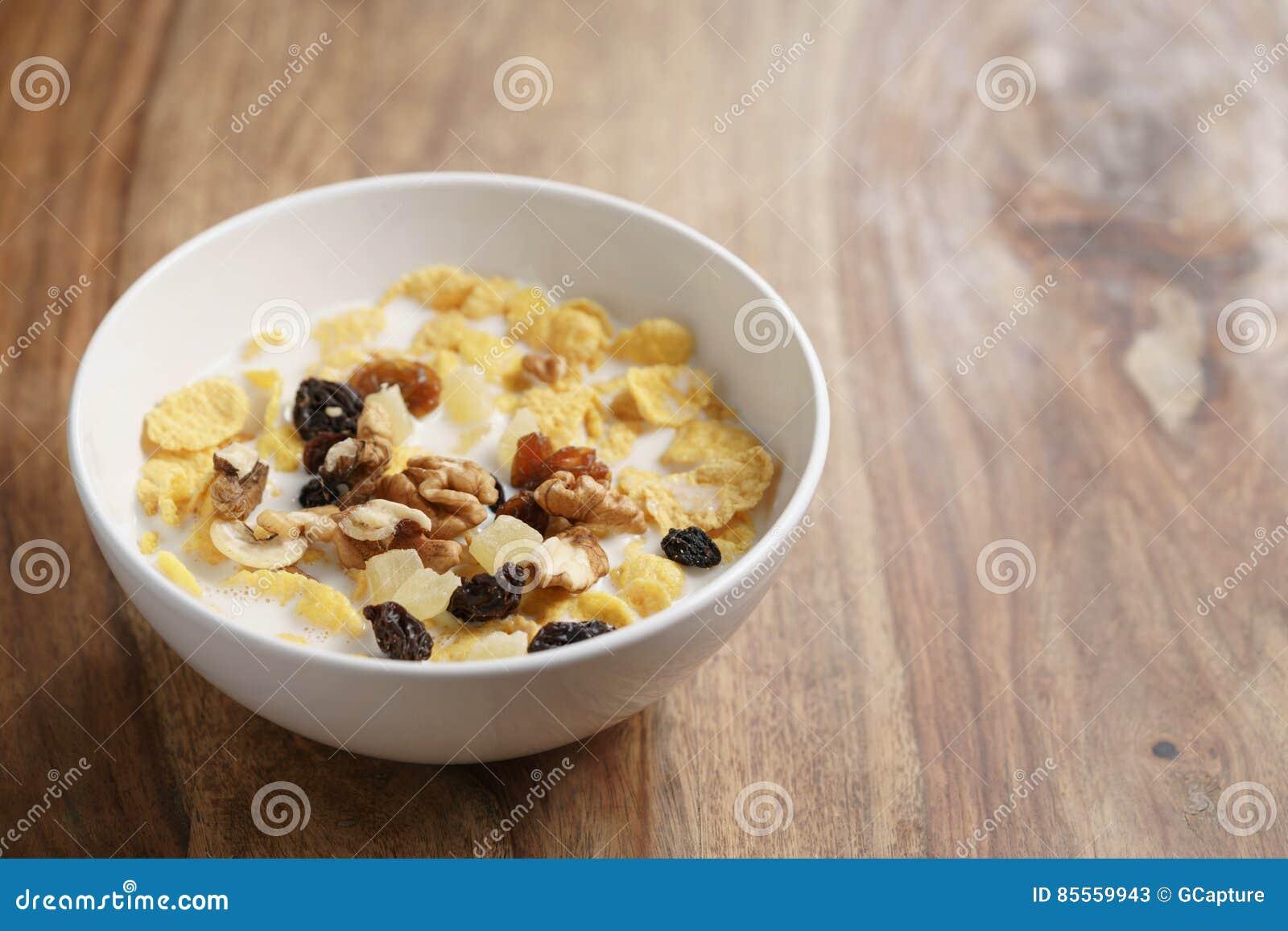 Corn Flakes mit Früchten und Nüssen in der weißen Schüssel auf hölzerner Tabelle mit Kopienraum