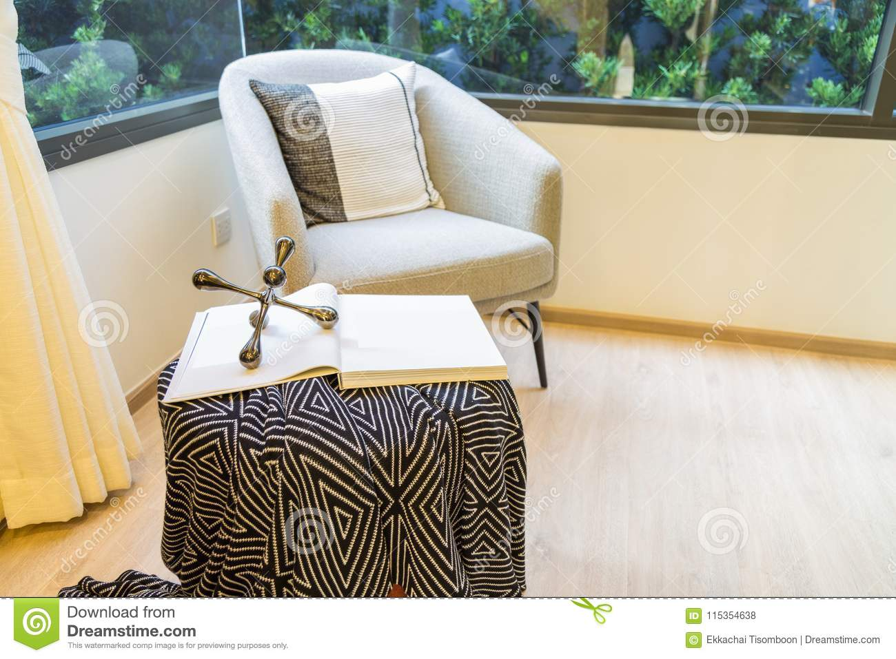 Corner Of Living Room With A Sofa Chair And A Book On Table