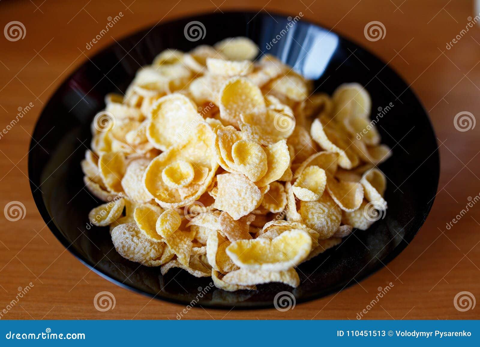 Cornflakes i en svart bunke Sund mat i morgonen