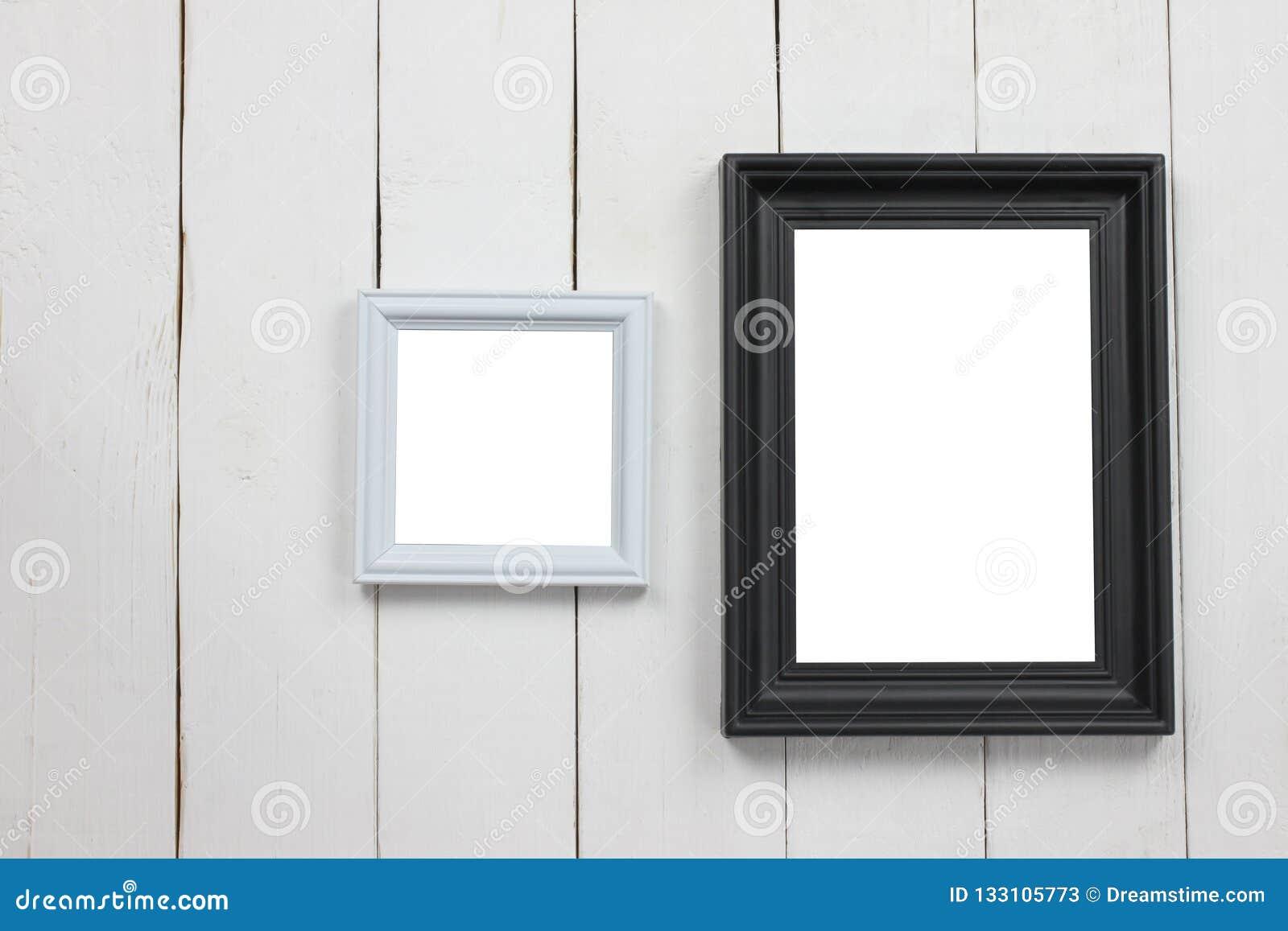 Cornice di legno stabilita dello spazio in bianco sul pavimento di legno bianco