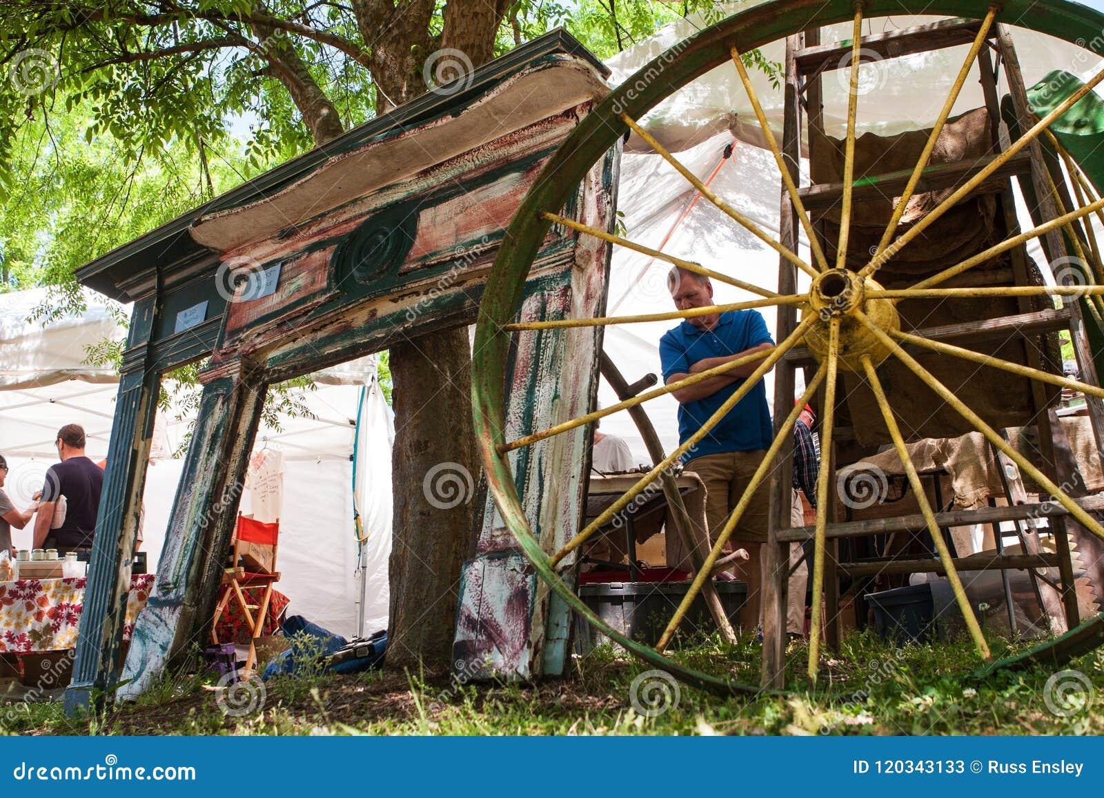 Cornijas de lareira da chaminé e rodas de vagão para a venda no festival antigo