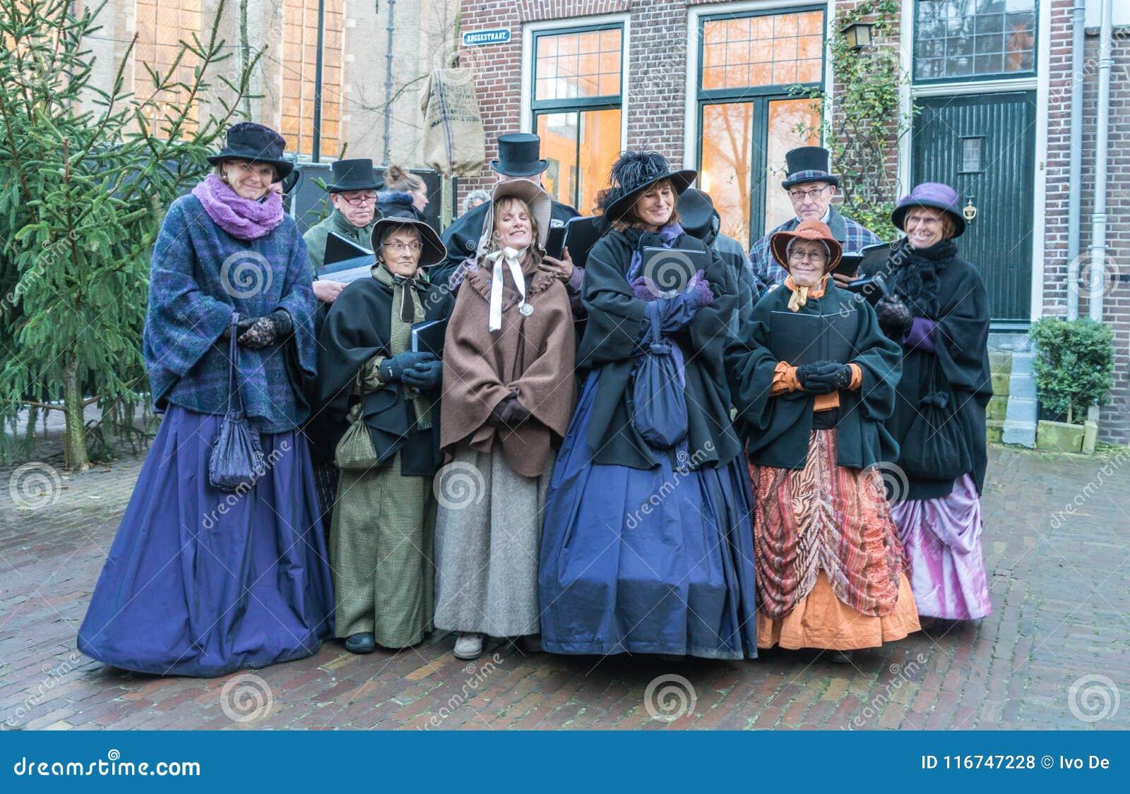 Coro dos atores vestidos que cantam dentro do festival de Dickens