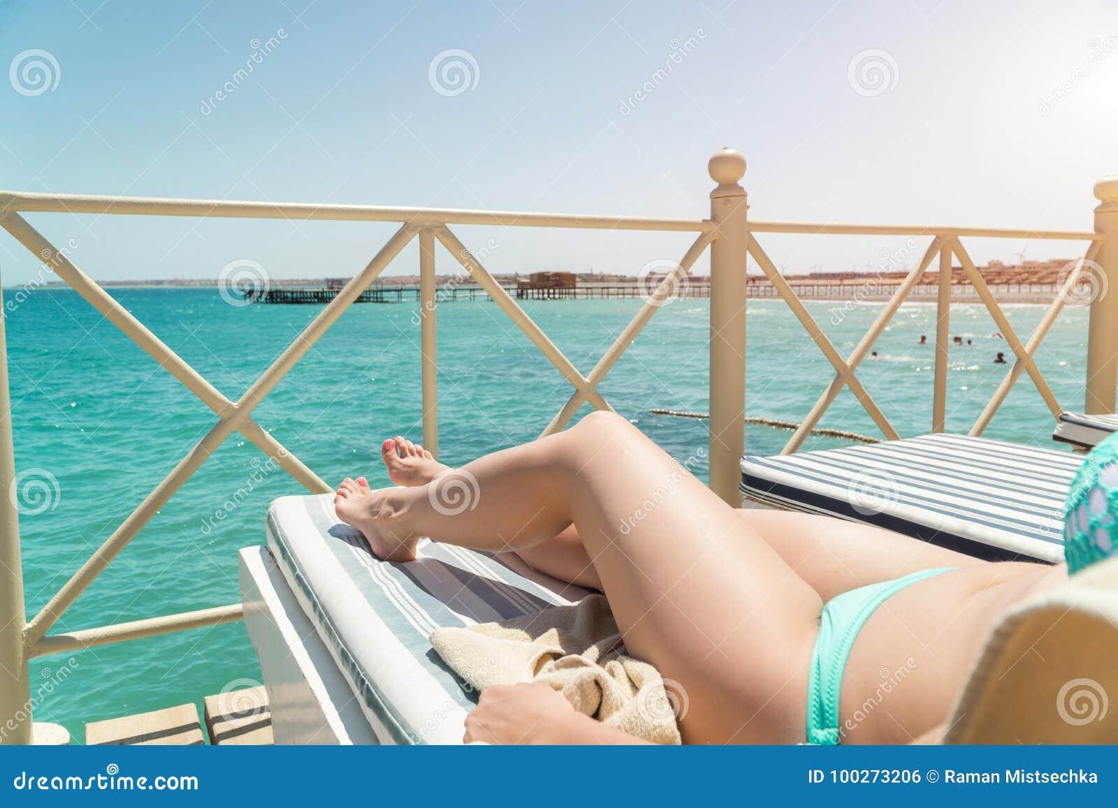 Corpo inferior das mulheres que encontra-se com creme do sunblock na forma para o conceito do cuidado da queimadura do câncer de