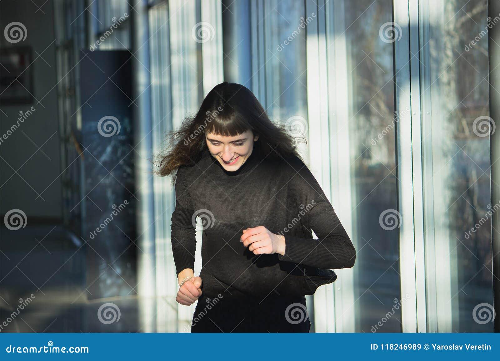 Corpo magro de uma jovem mulher bonita que veste calças de brim pretas