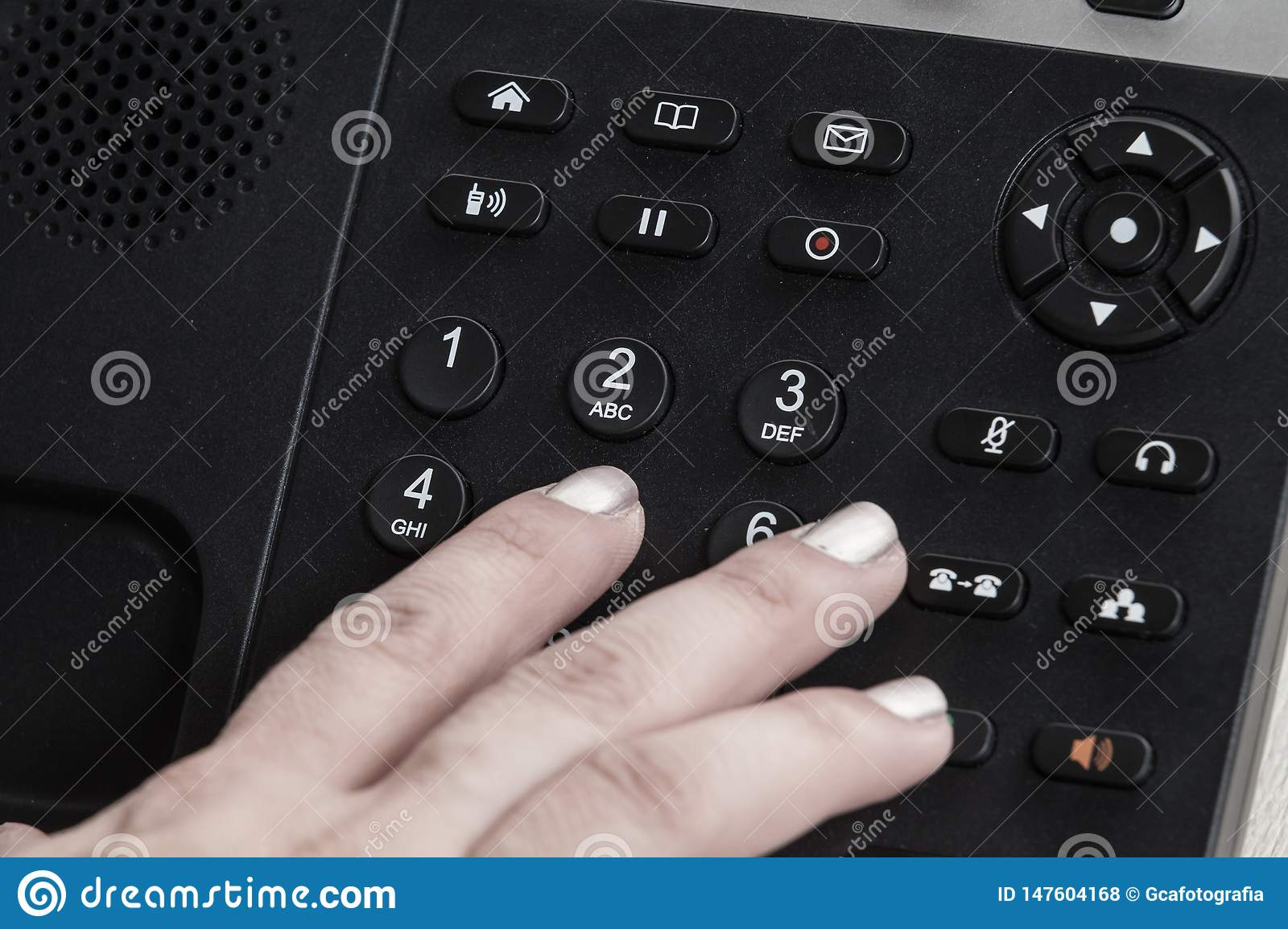 A close up woman hand dialing, a Black office IP Phone on a desk