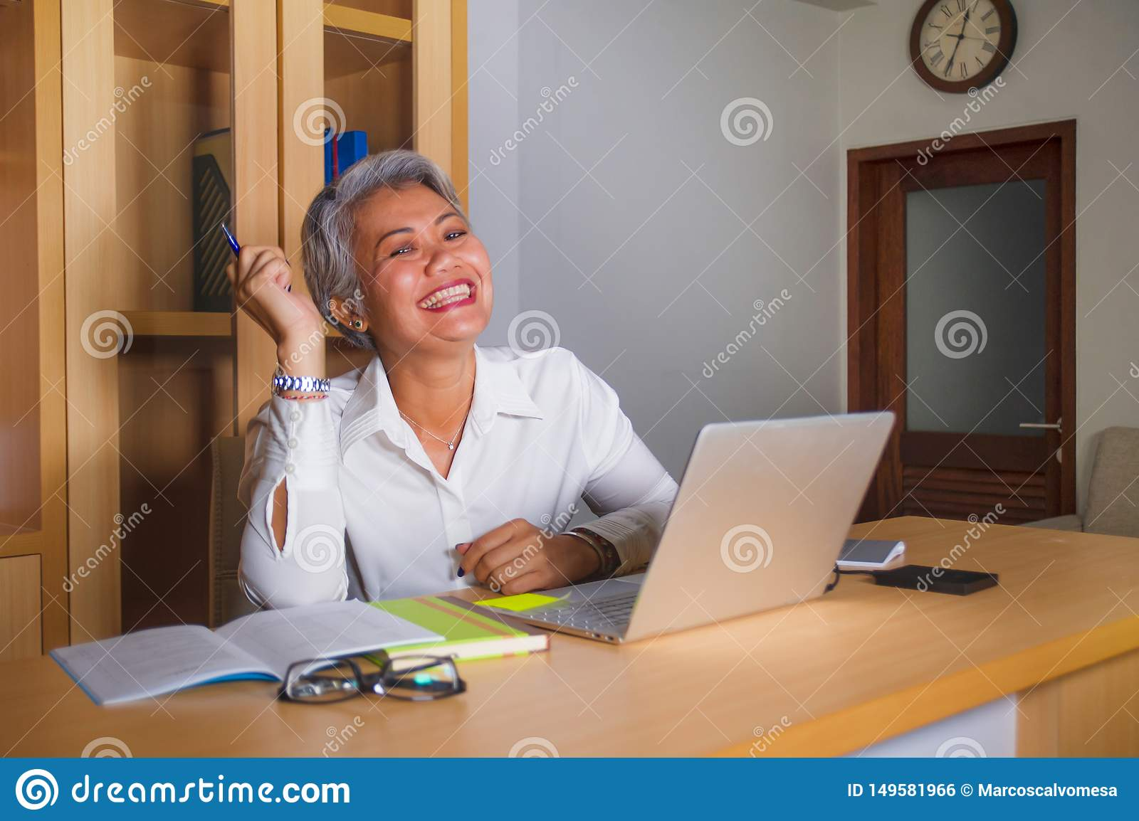 Corporate job lifestyle portrait of happy and successful attractive middle aged Asian woman working at office laptop computer desk