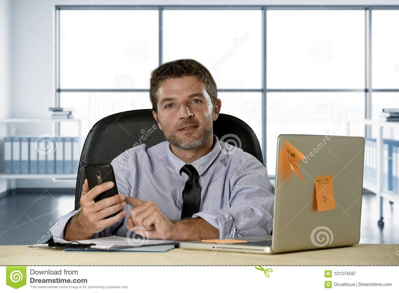 Corporate portrait of happy successful businessman in shirt and tie smiling at computer desk with mobile phone