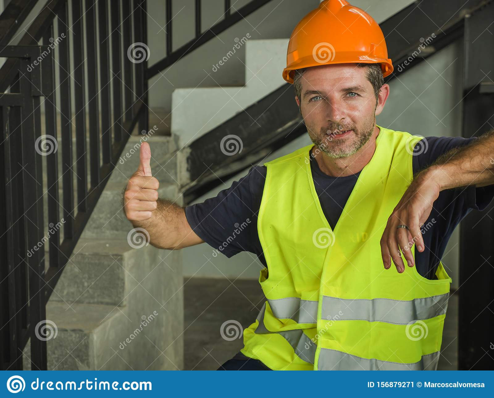 Corporate portrait of young attractive and happy builder man or constructor posing confident smiling wearing building helmet and