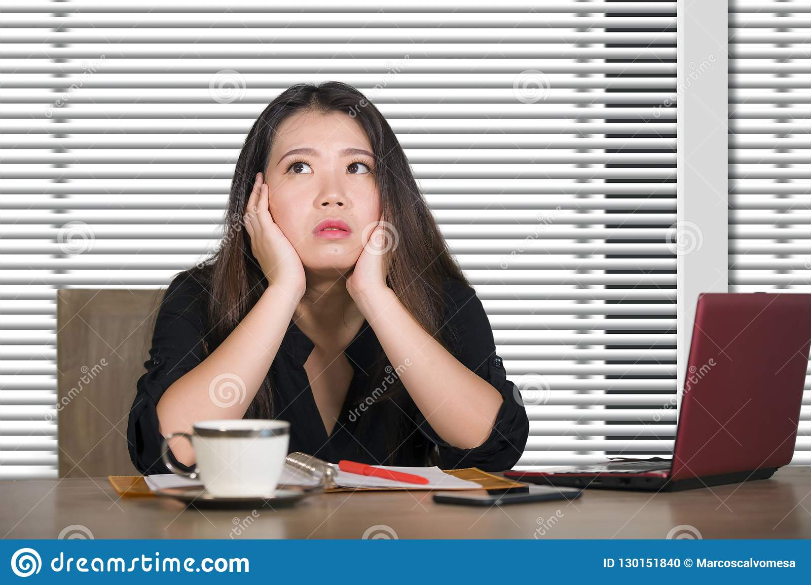 Corporate portrait of young attractive sad and stressed Asian Korean woman working at company office computer desk feeling depress