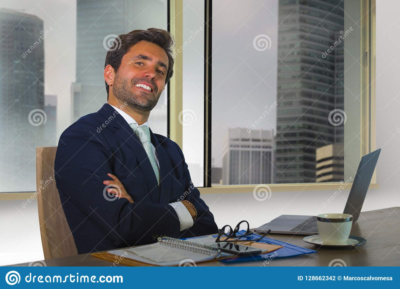 Corporate portrait of young happy handsome and attractive businessman working at computer desk in modern office at central busines