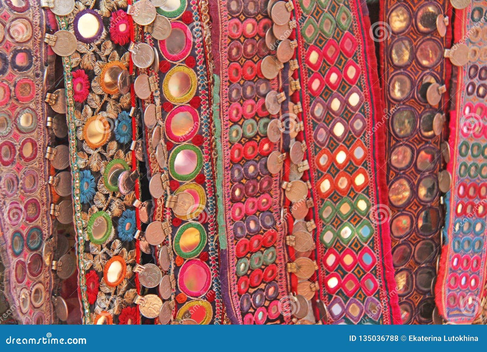 Correas étnicas coloridas con los espejos en el mercado en GOA, la India Recuerdos tibetanos