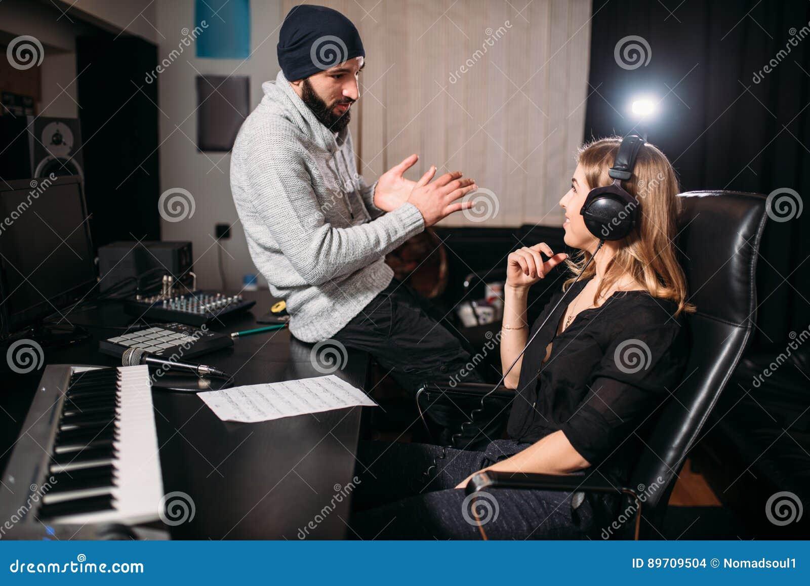 Correcte producent met vrouwelijke zanger in muziekstudio