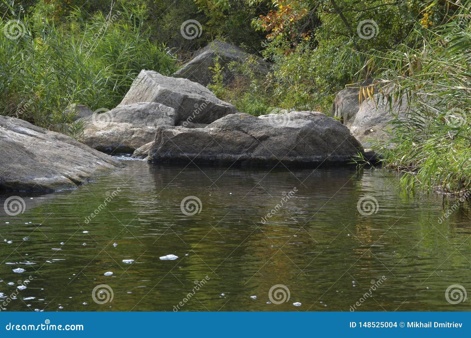 Corredeira de pedra no rio Deadwater/Mertvovod em que fluxos ao longo da parte inferior da garganta de Aktovsky