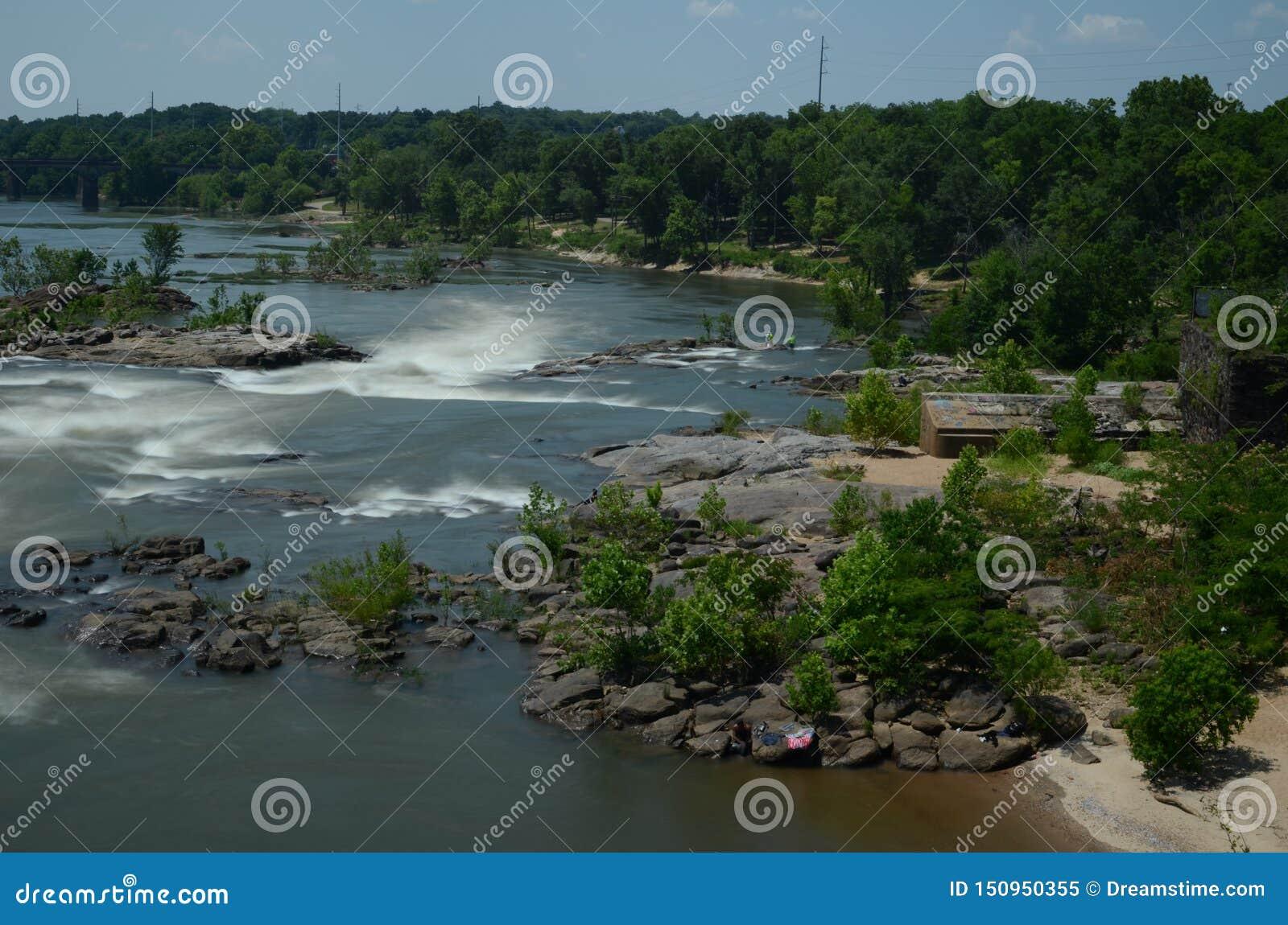 Corredeira do rio no movimento com madeiras e no verde em torno dele