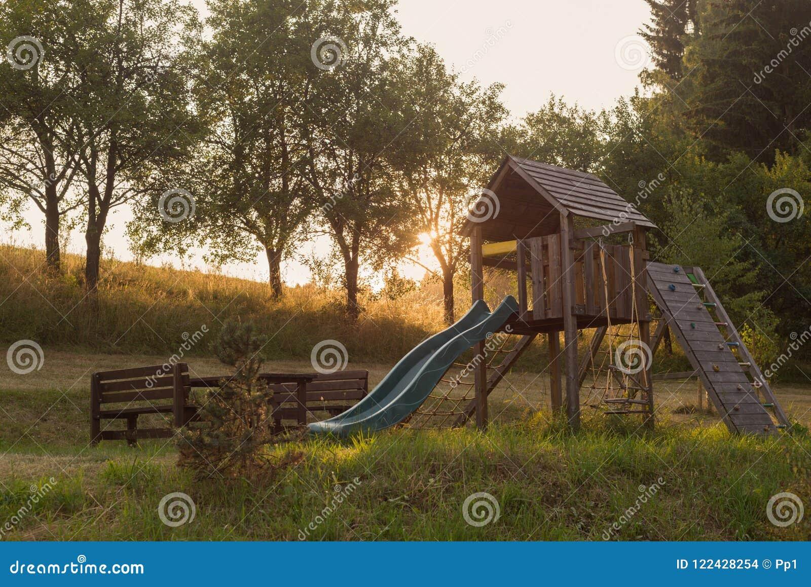 Corrediça exterior de madeira no parque rural do jardim, por do sol do campo de jogos das crianças