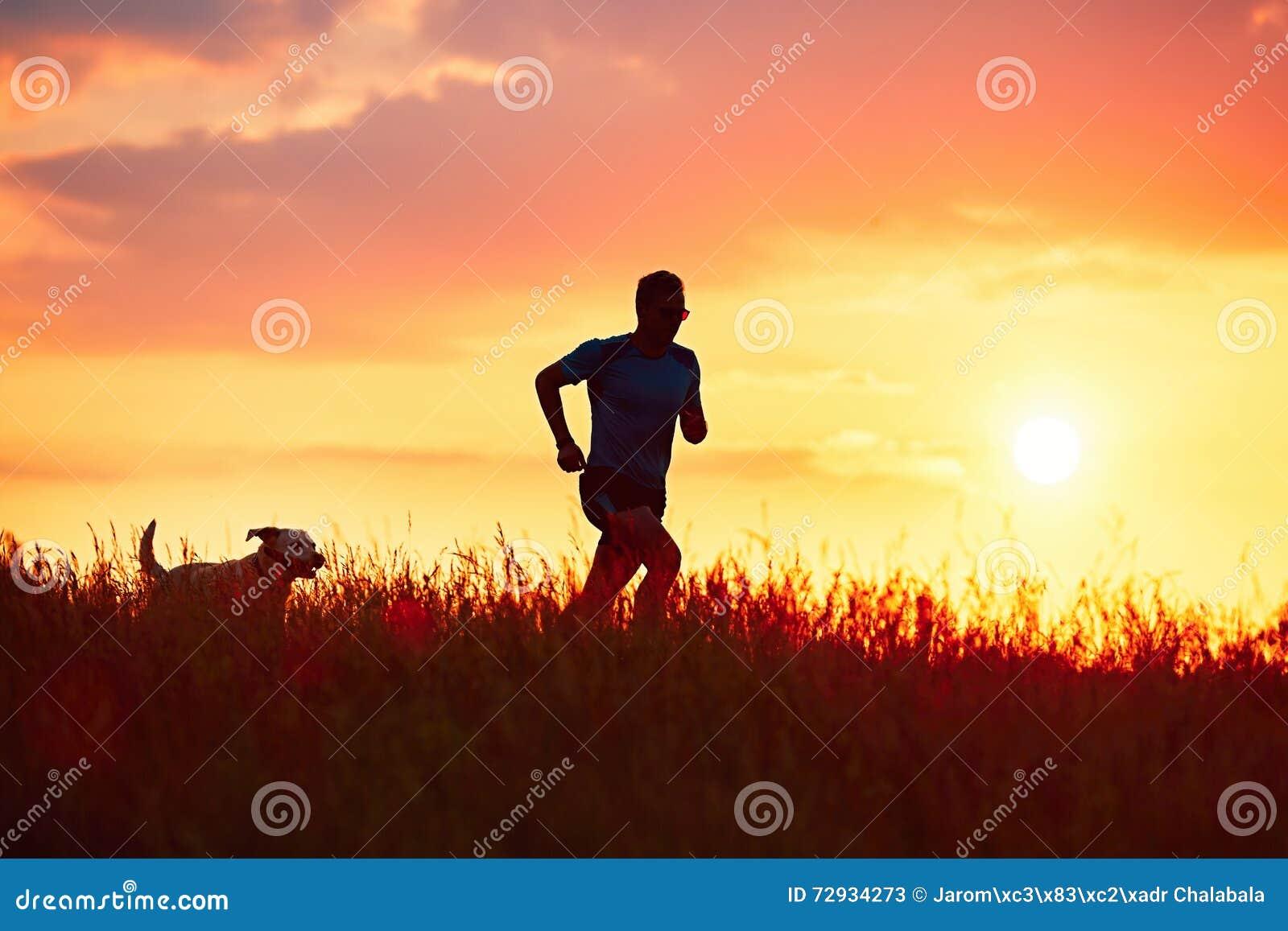 Corredor atlético com o cão no por do sol