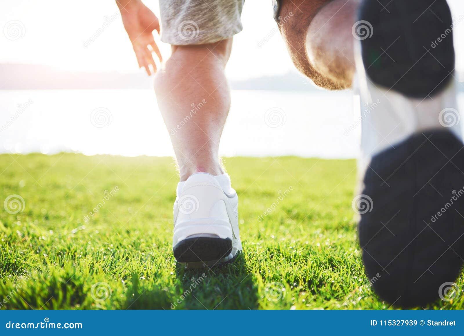 Corredor através dos campos exterior no conceito da luz do sol do verão para o exercício, a aptidão e o estilo de vida saudável F