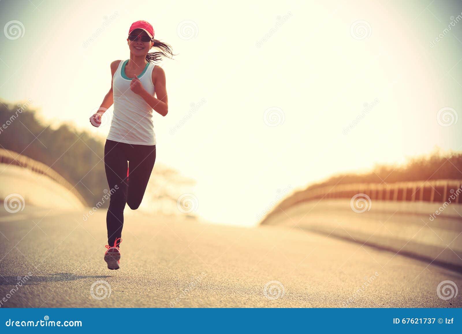 Corredor da fuga da mulher da aptidão que corre na estrada de cidade