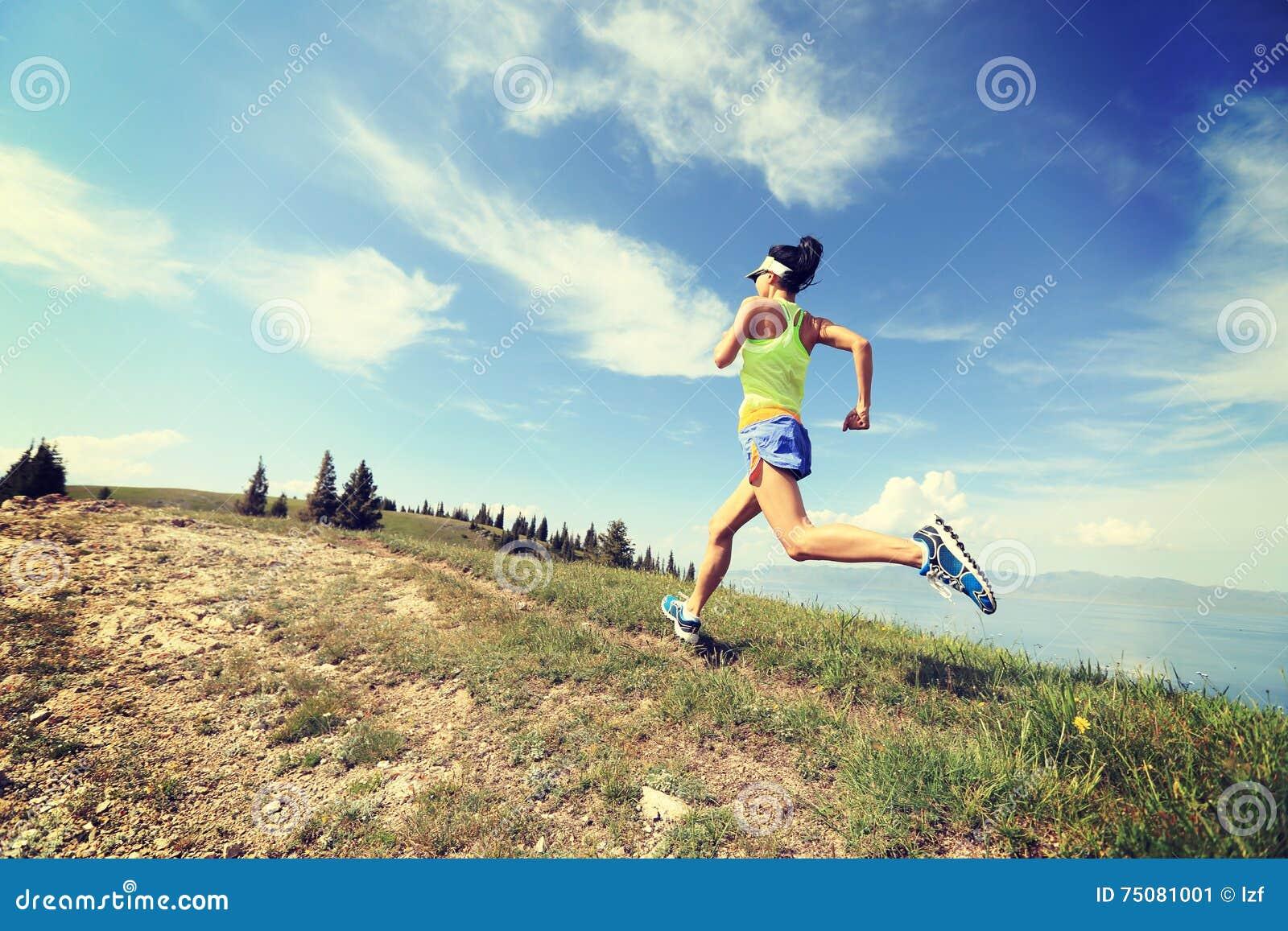 Corredor da fuga da mulher que corre no pico de montanha bonito