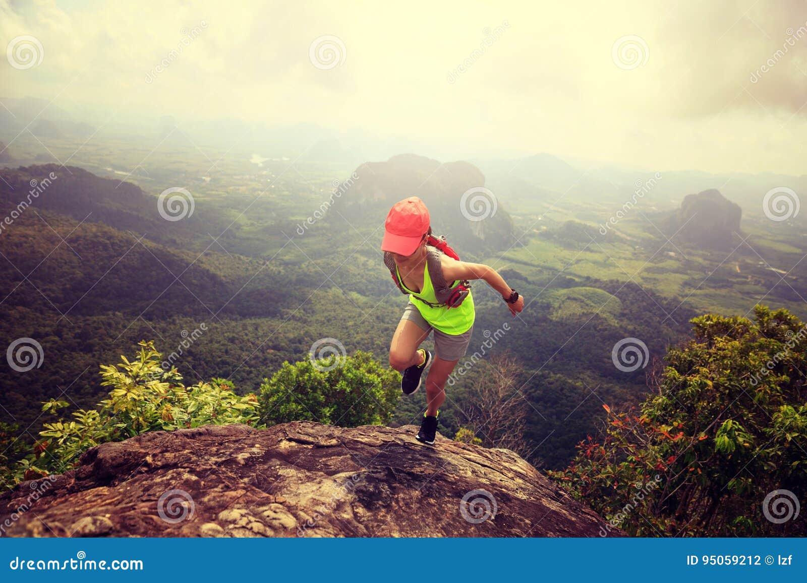 Corredor da fuga da mulher que corre na parte superior da montanha