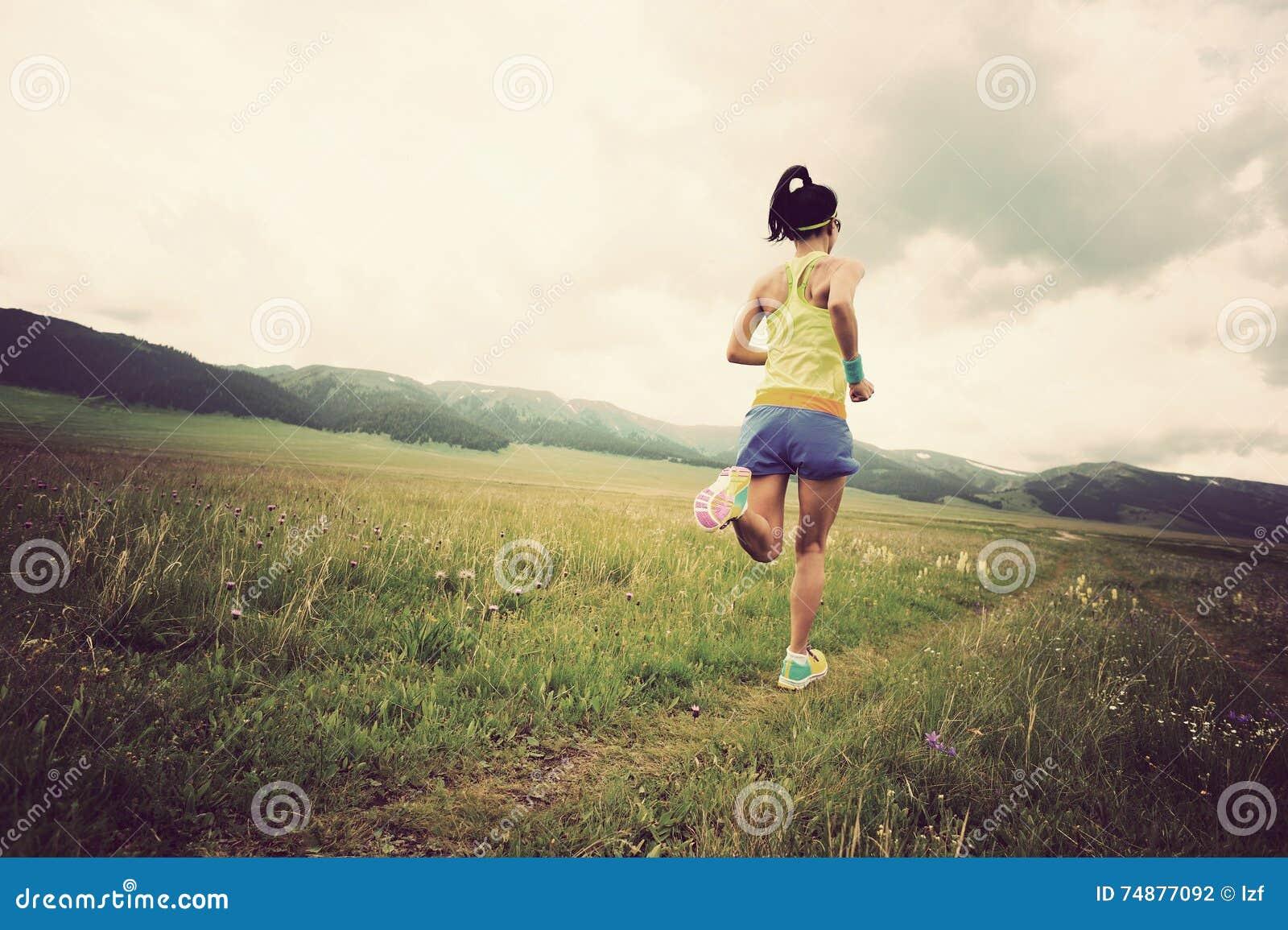 Corredor da jovem mulher que corre na estrada bonita