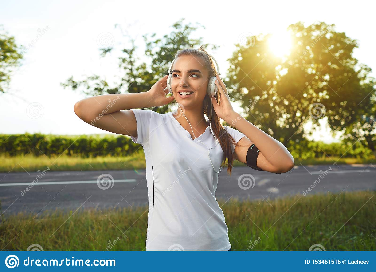 Corredor da menina com os auriculares que descansam antes de movimentar-se na estrada