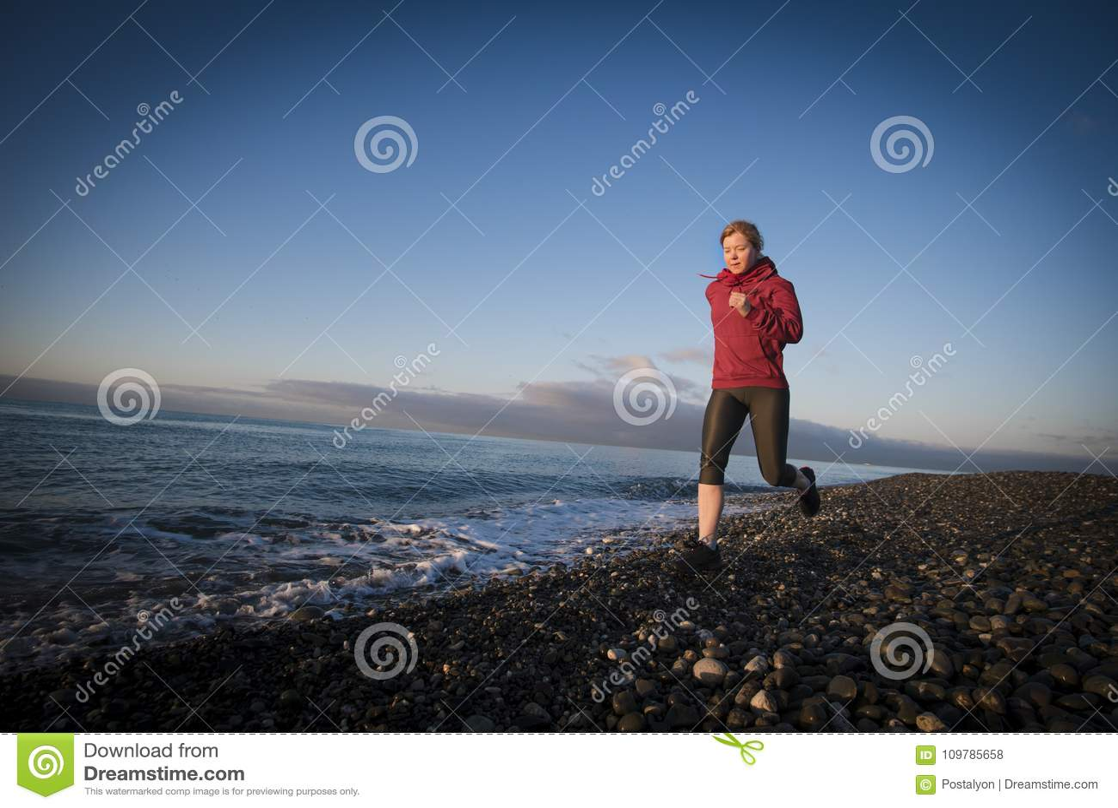Corredor da mulher adulta que corre no beira-mar do nascer do sol Estilo de vida saudável