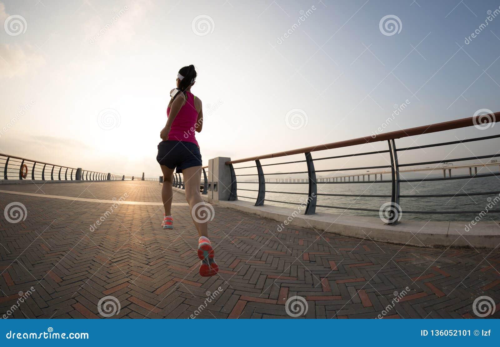 Corredor da mulher na fuga do beira-mar