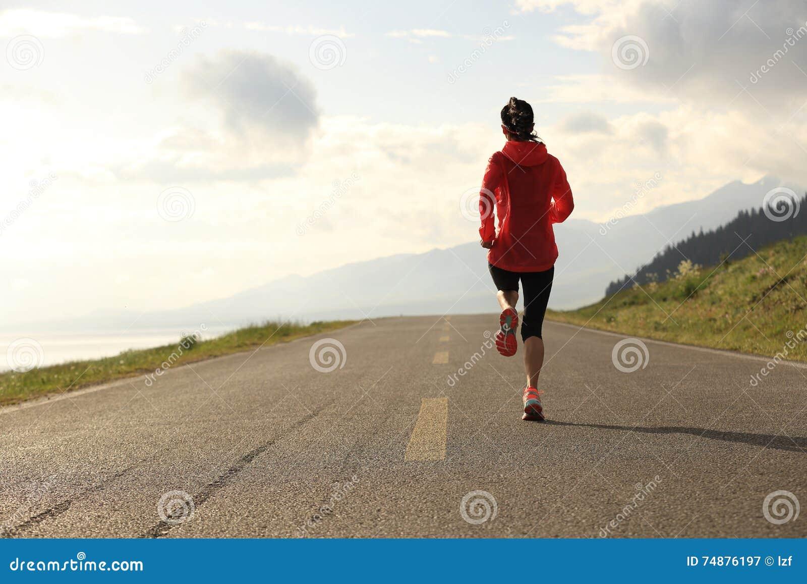 Corredor da mulher que corre na estrada
