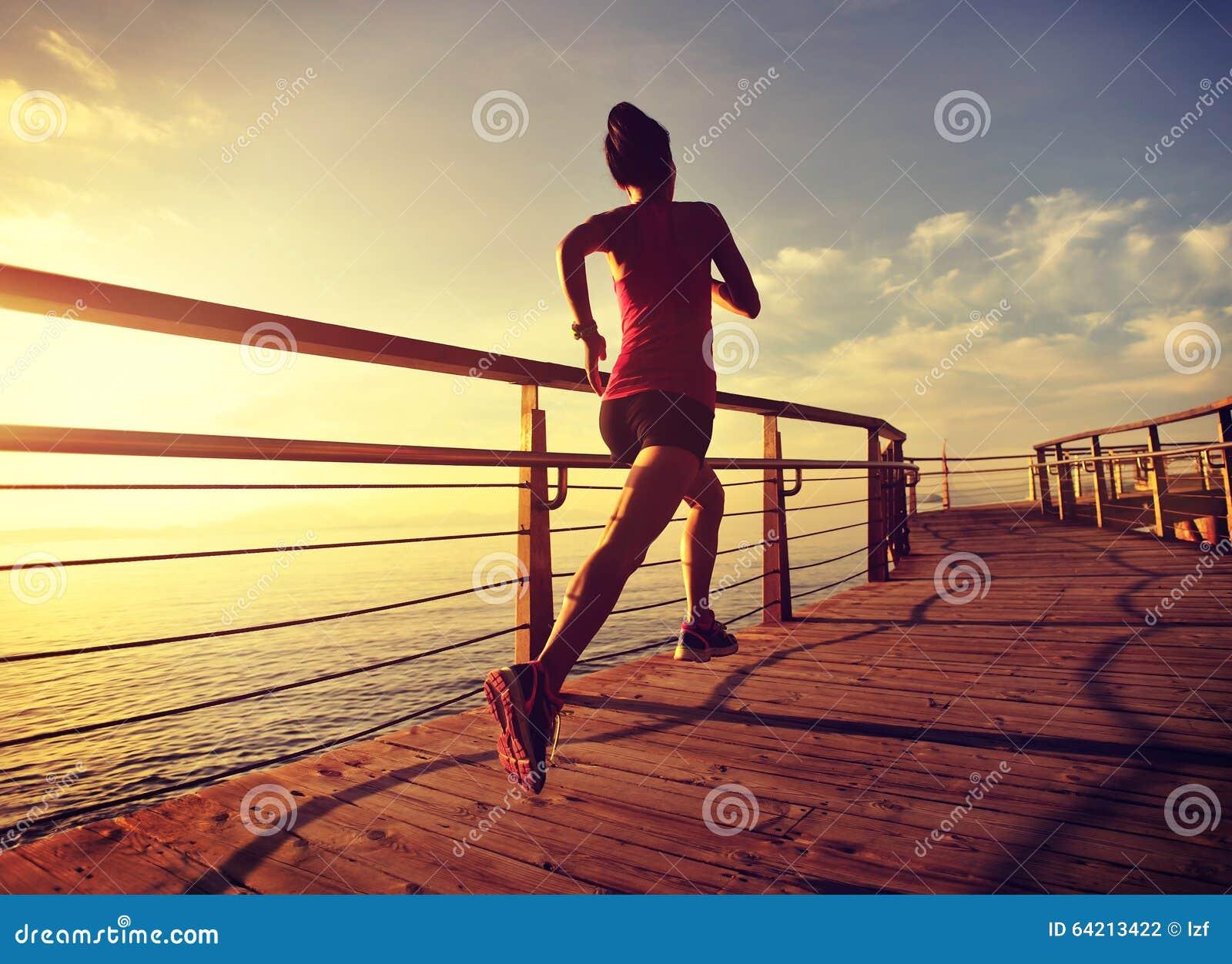 Corredor de la mujer de la aptitud que corre en el paseo marítimo de la playa