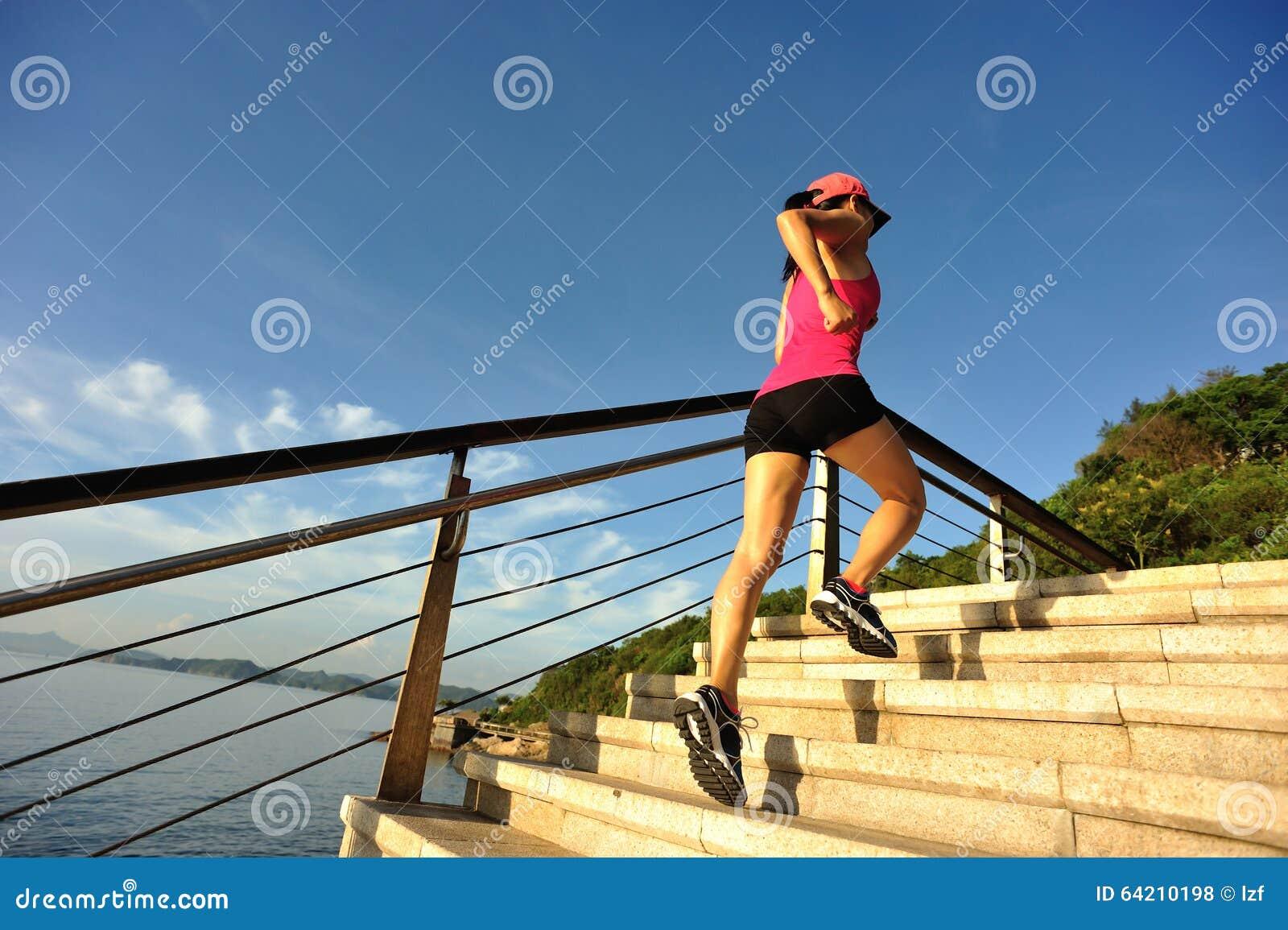 Corredor de la mujer de la aptitud que corre en las escaleras de la piedra de la playa