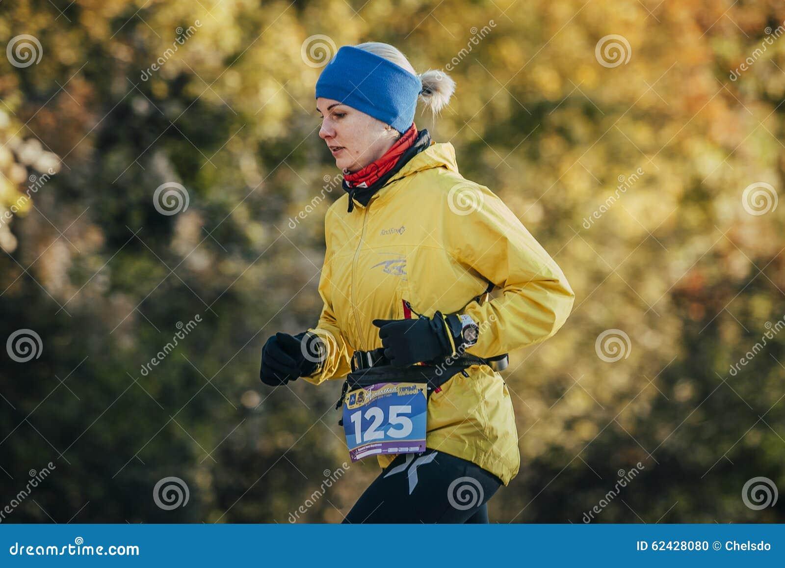 Corredor de la mujer joven que corre en bosque del otoño