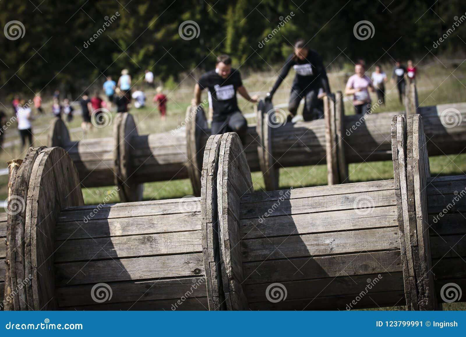 Corredor de raça enlameado do obstáculo na ação Corrida da lama