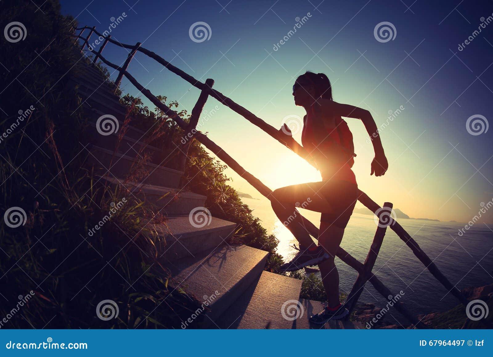 Corredor del rastro de la mujer que corre para arriba en las escaleras de la montaña