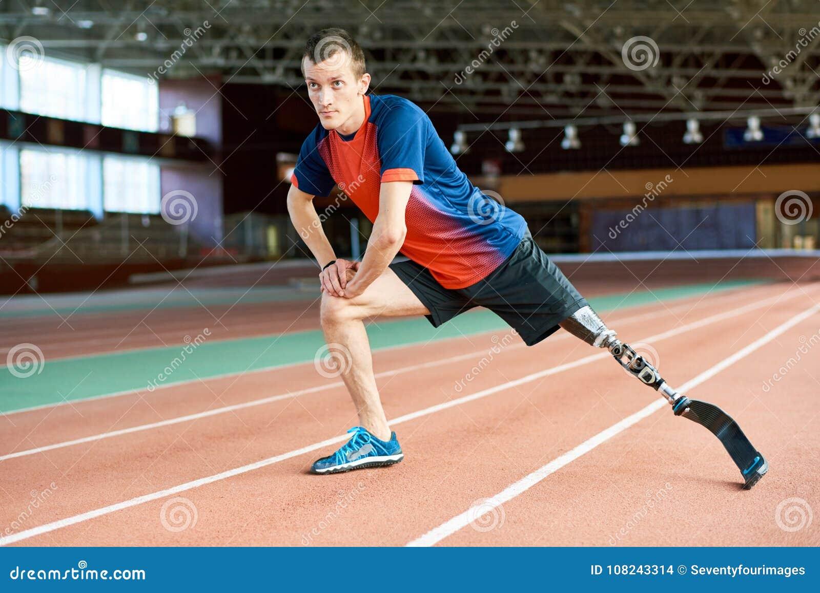 Corredor discapacitado que estira en estadio