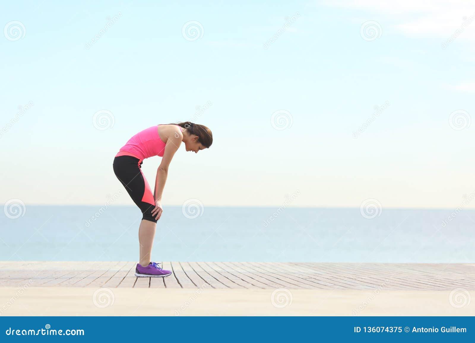 Corredor esgotado que descansa na praia após o exercício