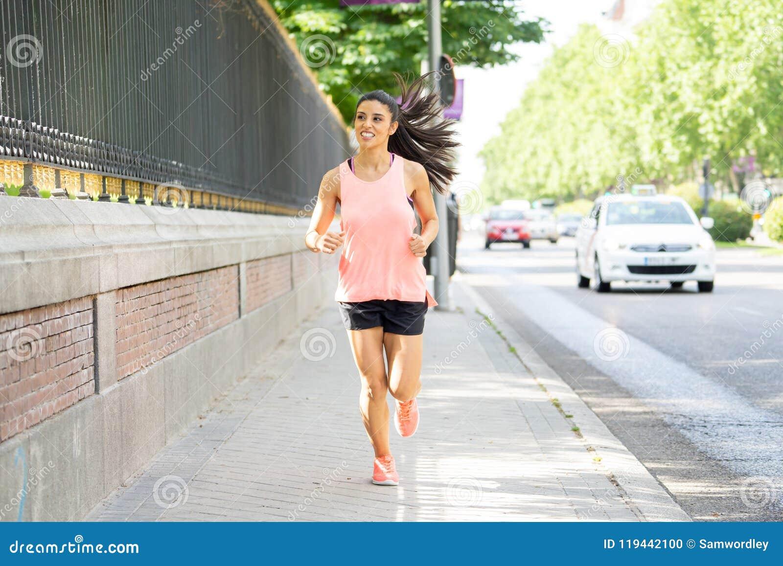 Corredor fêmea latin novo atrativo que movimenta-se na rua da cidade no conceito da aptidão