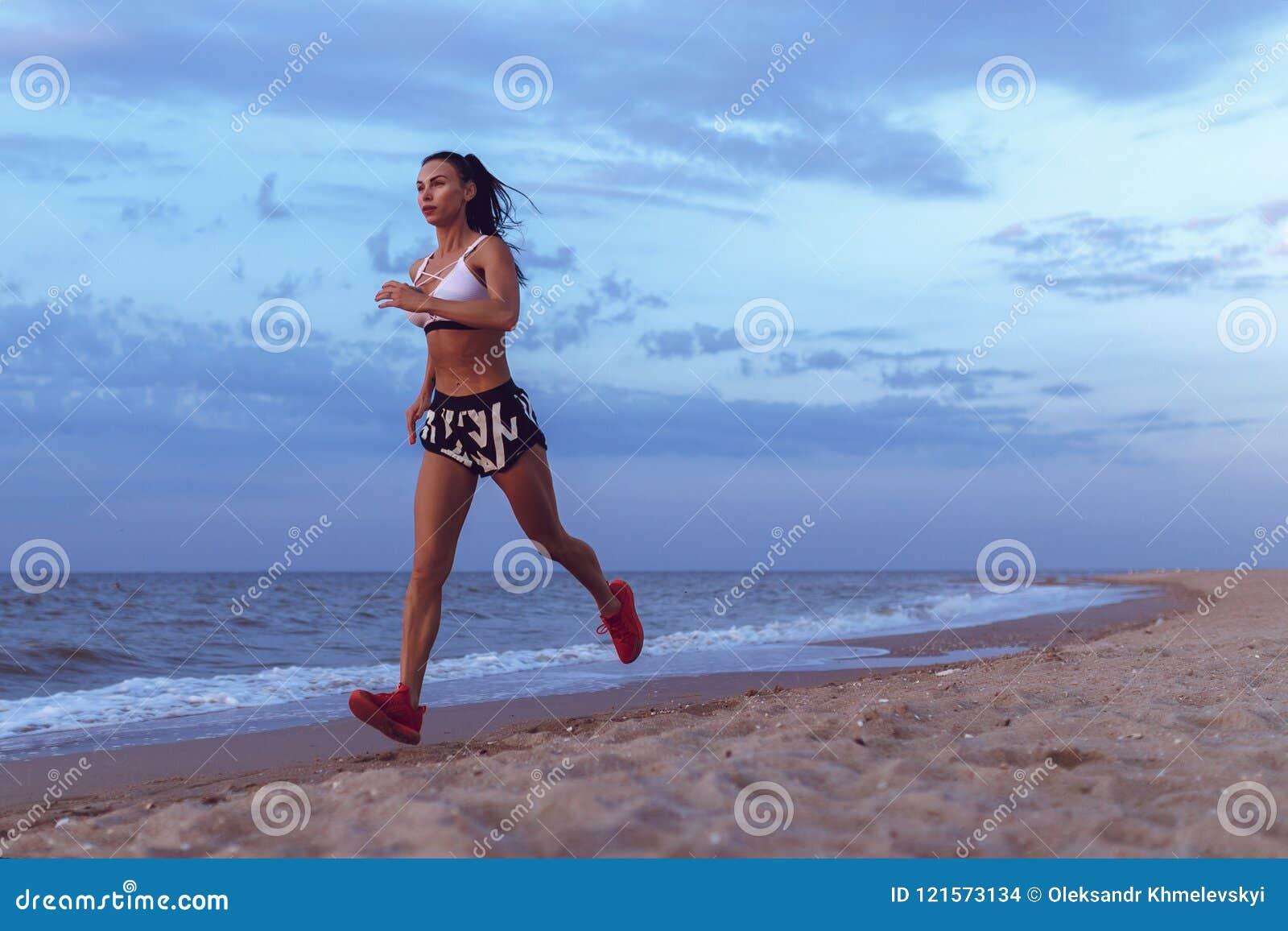 Corredor novo saudável da fuga da mulher da aptidão que corre no beira-mar do nascer do sol