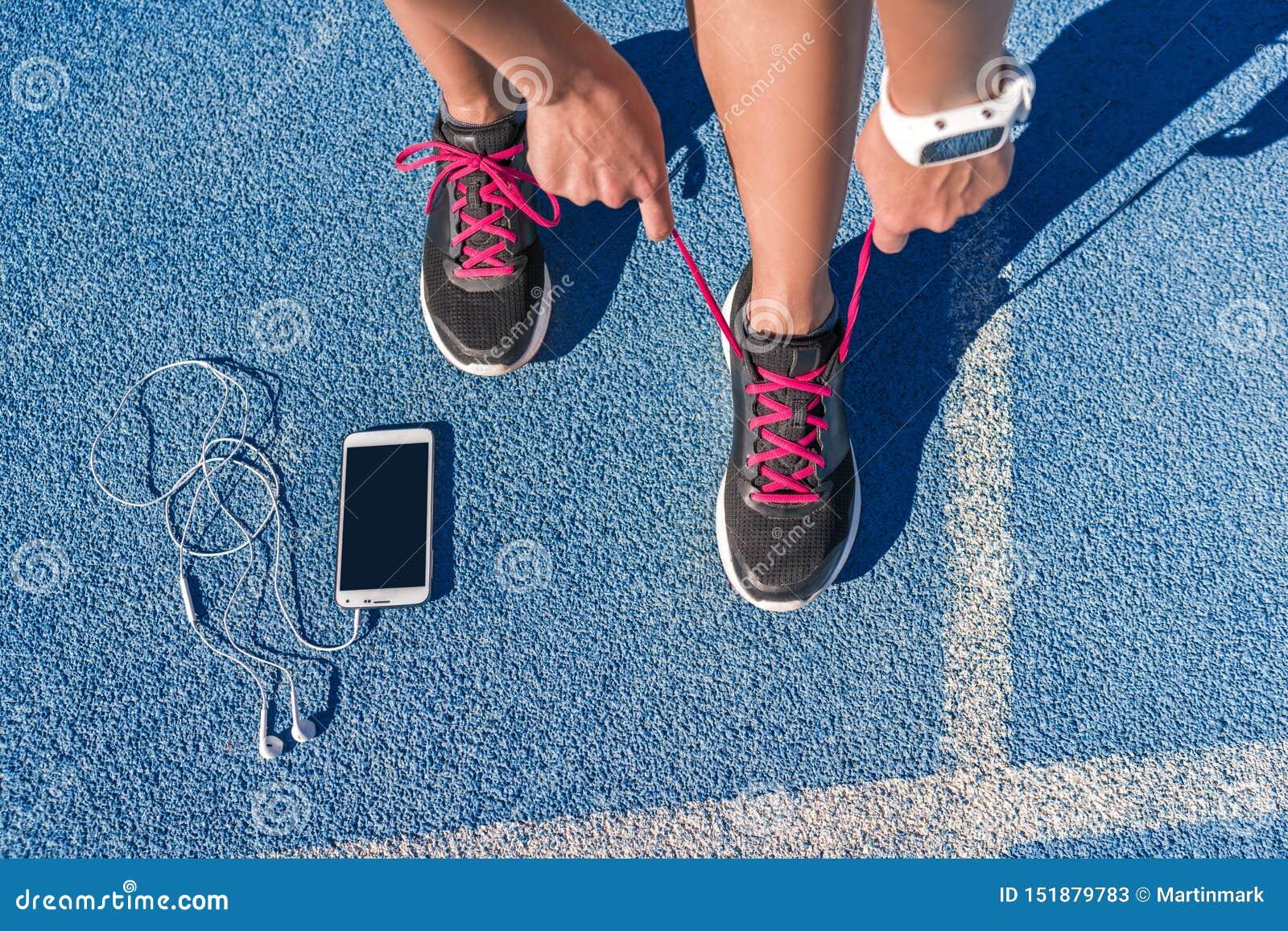 Corredor que ata cordones de zapatillas deportivas en pista del funcionamiento de la raza