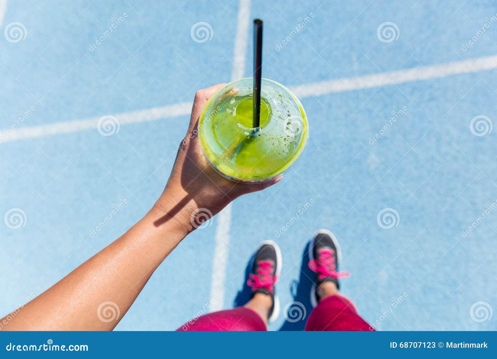 Corredor que bebe um batido verde na pista de atletismo