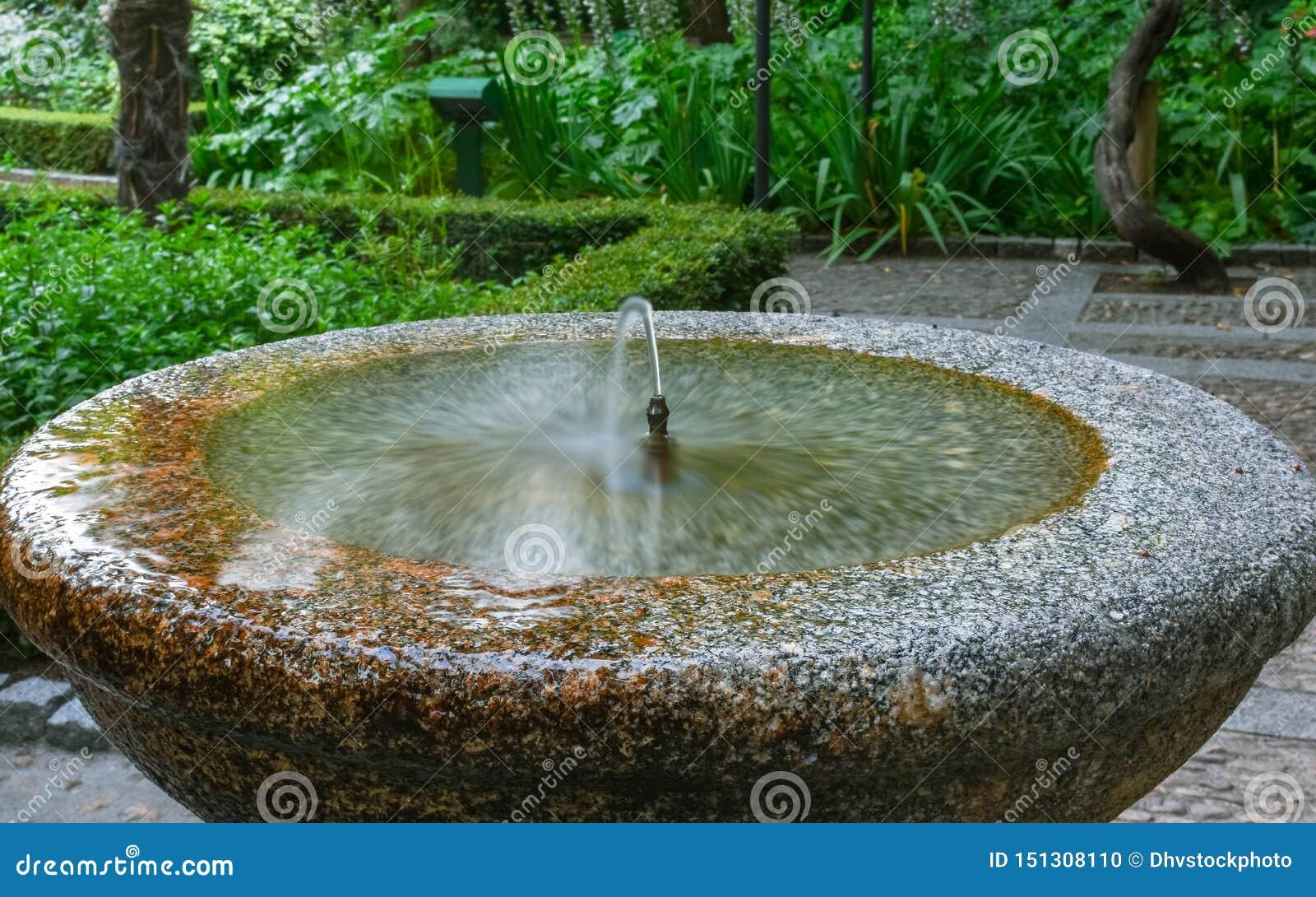 Corrente a getto dell acqua potabile della fontana di pietra