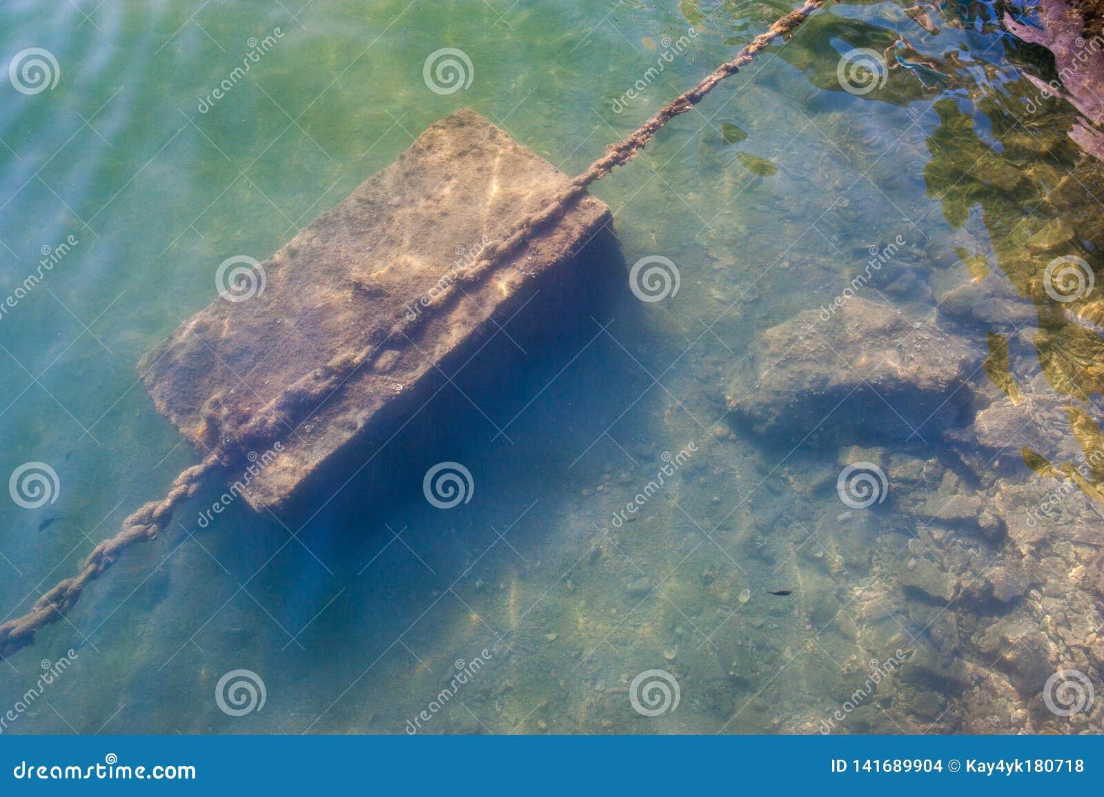 Corrente oxidada sob a água, âncora amarre na costa