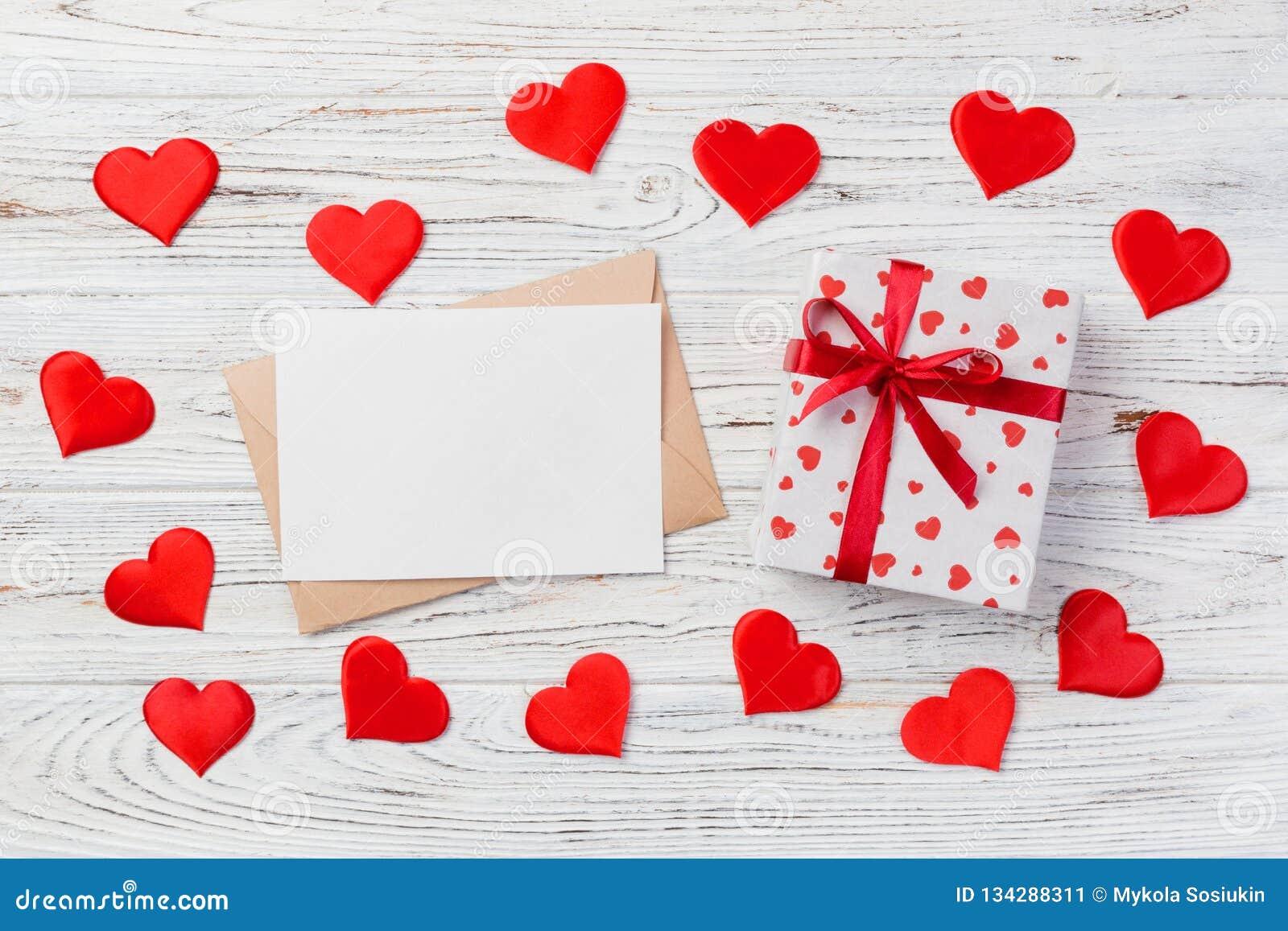 Correo del sobre con la caja roja del corazón y de regalo sobre el fondo de madera blanco Concepto del saludo de Valentine Day Ca