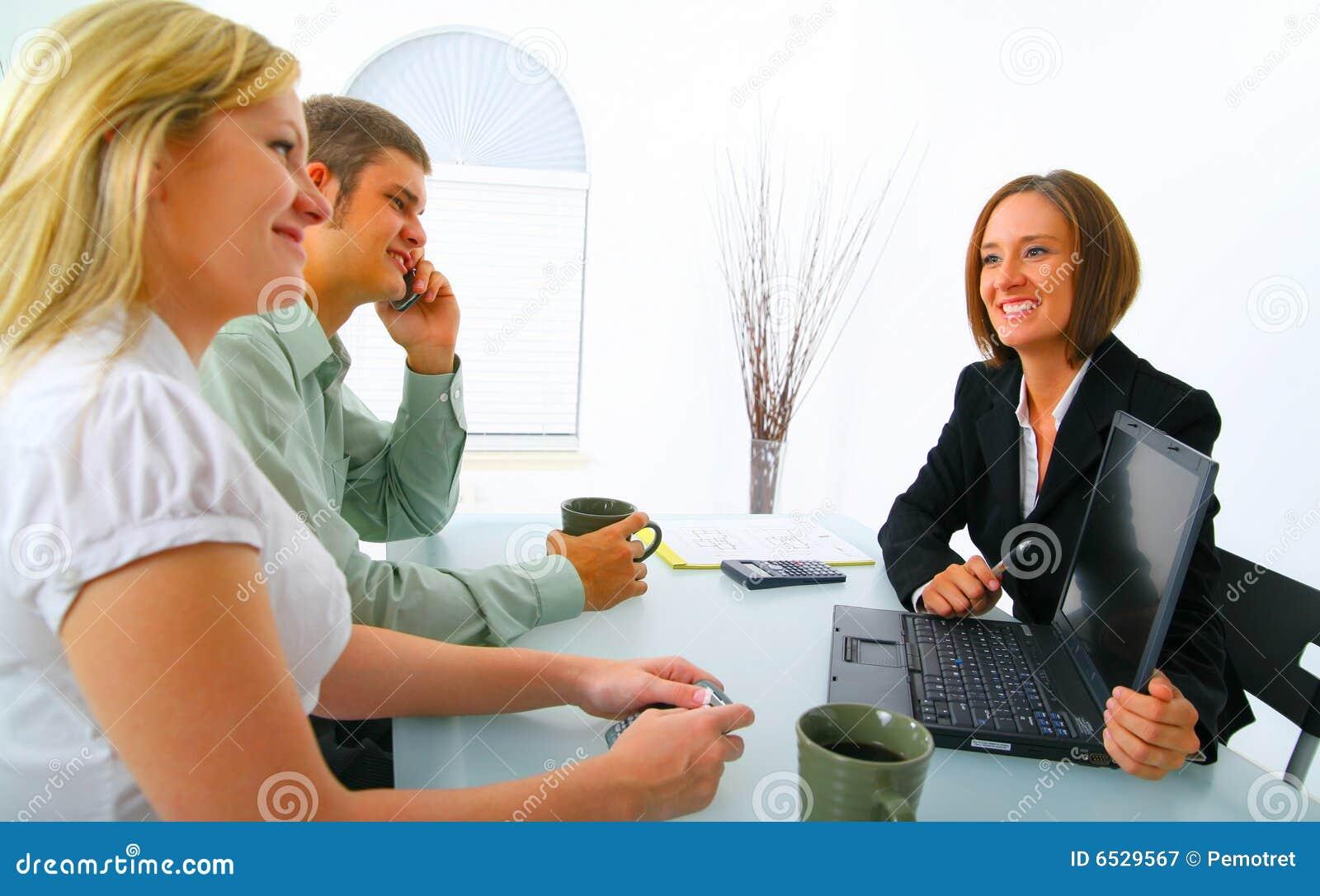 Corretor de bens imobiliários que mostra o portátil aos clientes