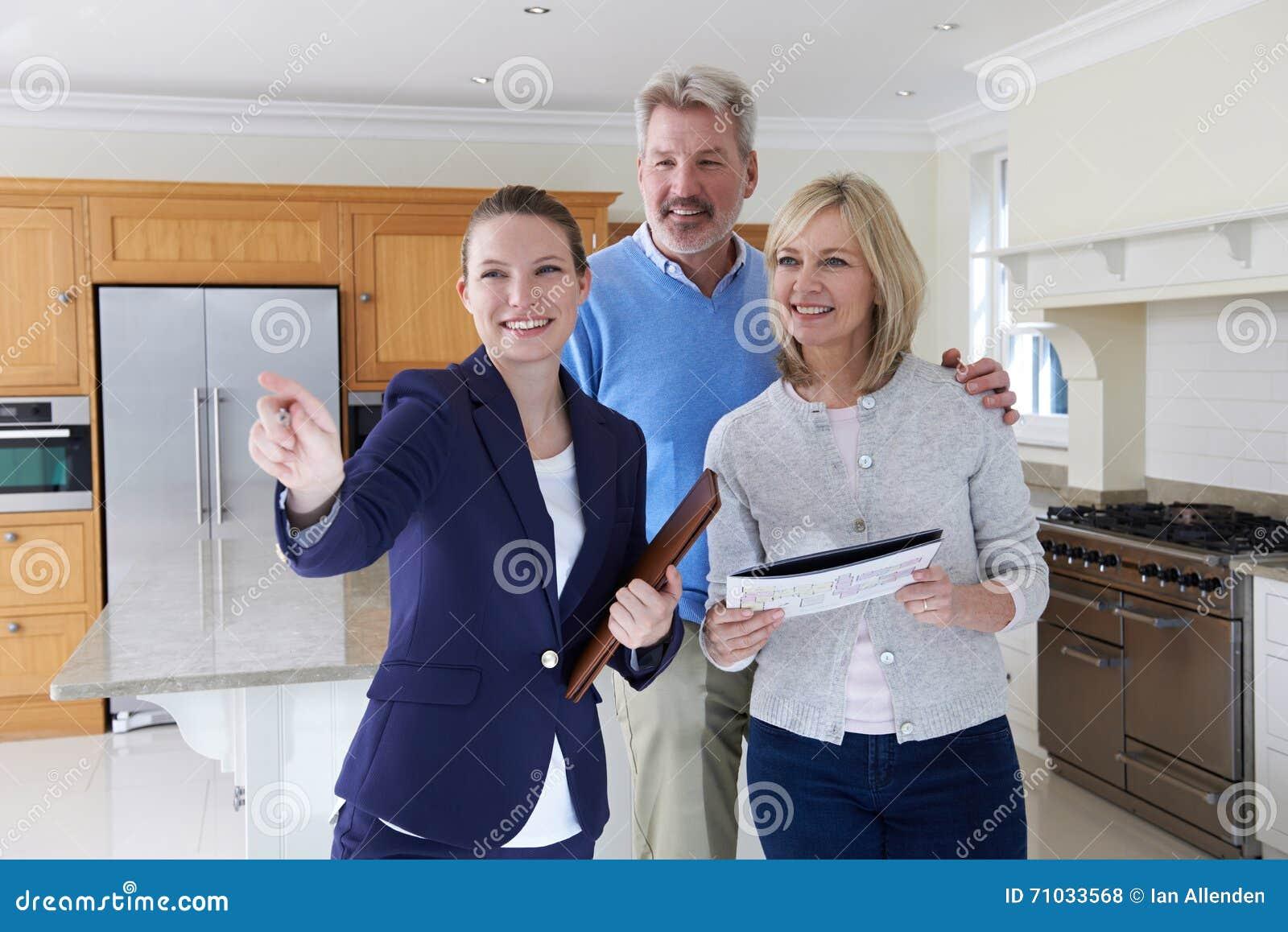 Corretor de imóveis fêmea que mostra pares maduros em torno da casa