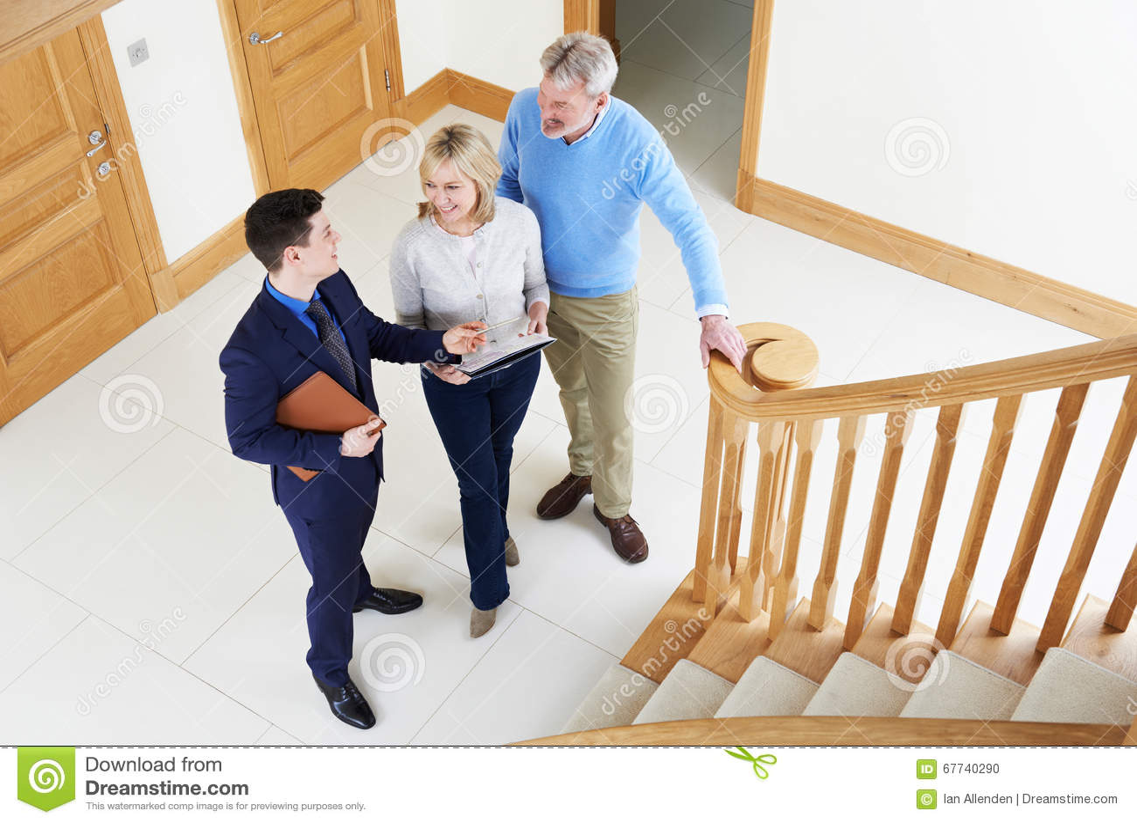 Corretor de imóveis que mostra pares maduros em torno da casa para a venda