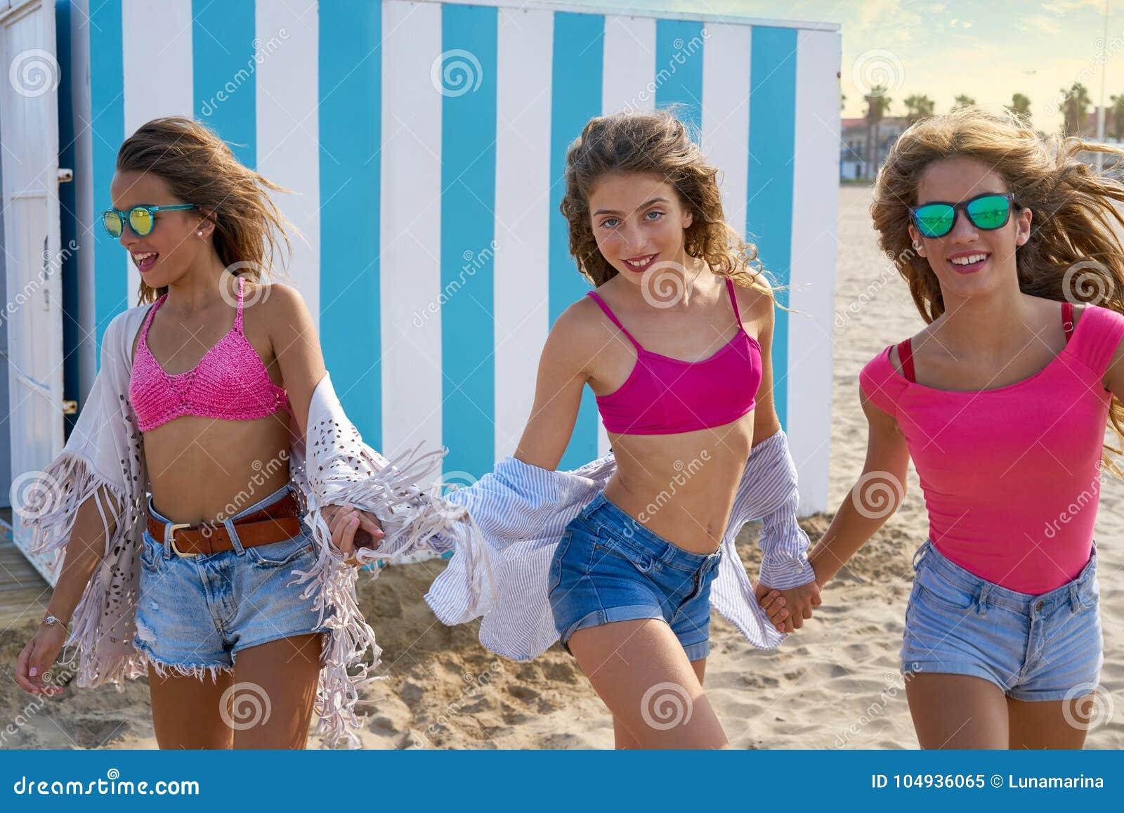 Corrida adolescente das meninas dos melhores amigos feliz na praia